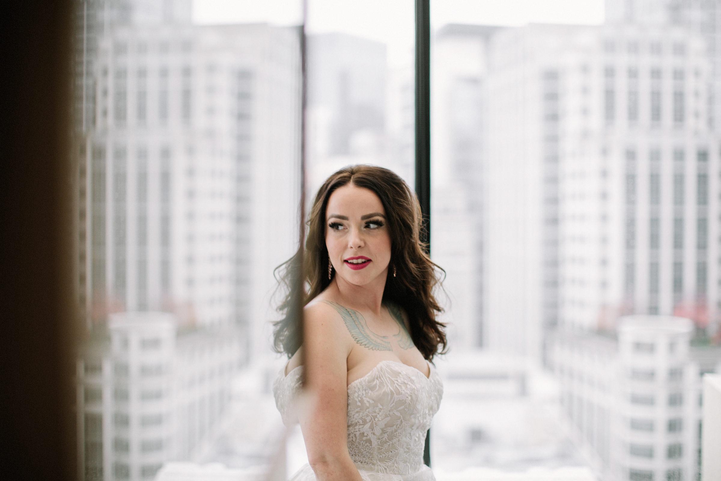 Bride against white cityscape through window - photo by Jonas Seaman Photography