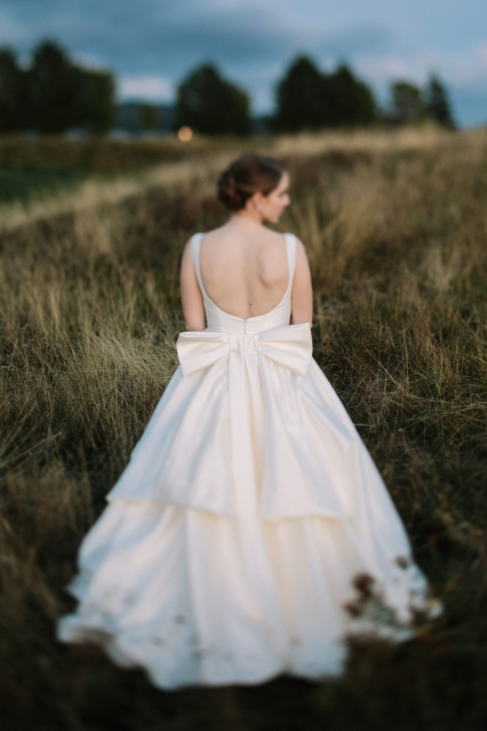Bride outdoors in backless satin gown with big bow - photo by Jonas Seaman Photography