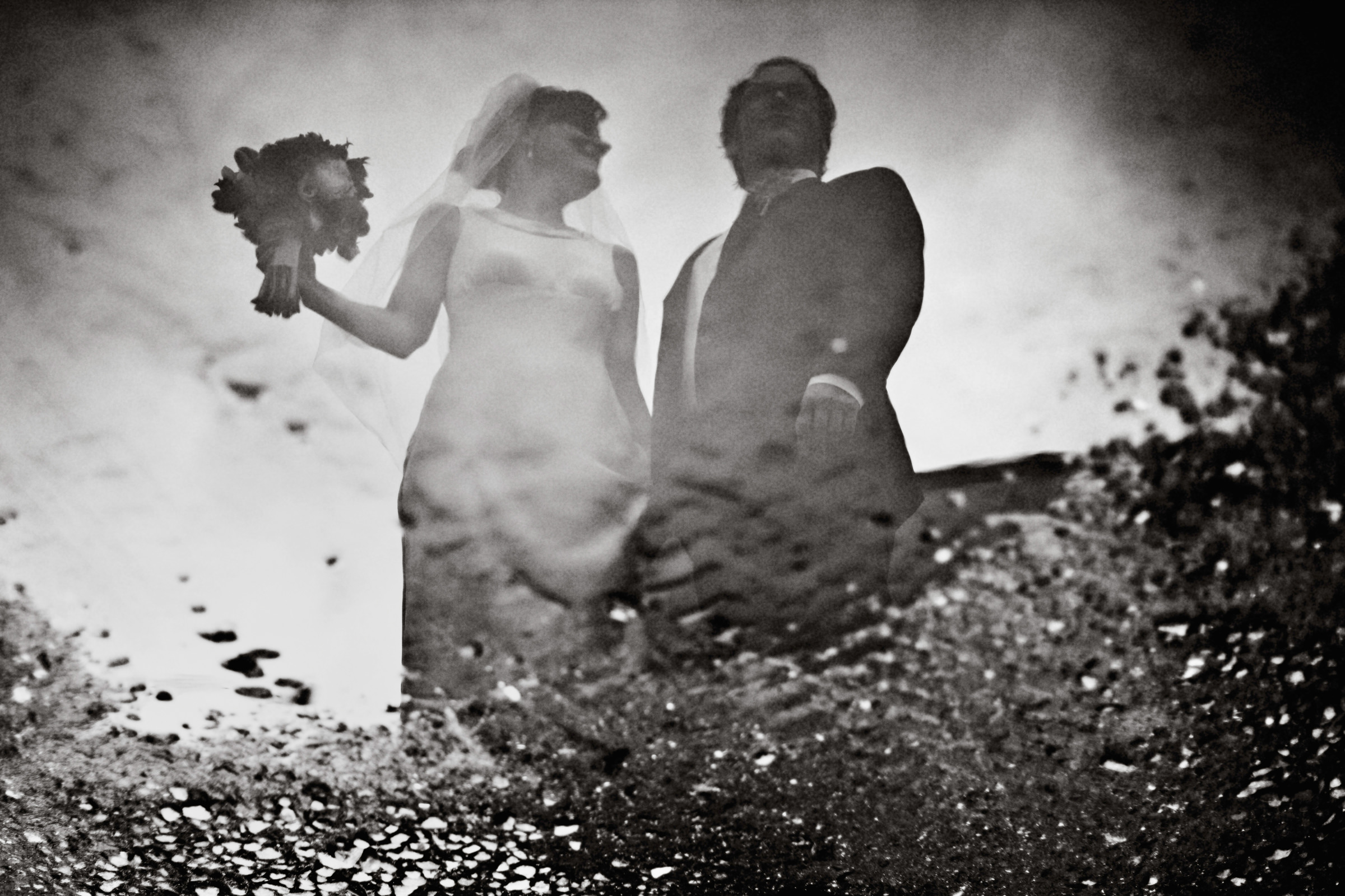 Reflection of couple through surf spray - photo by Jonas Seaman Photography