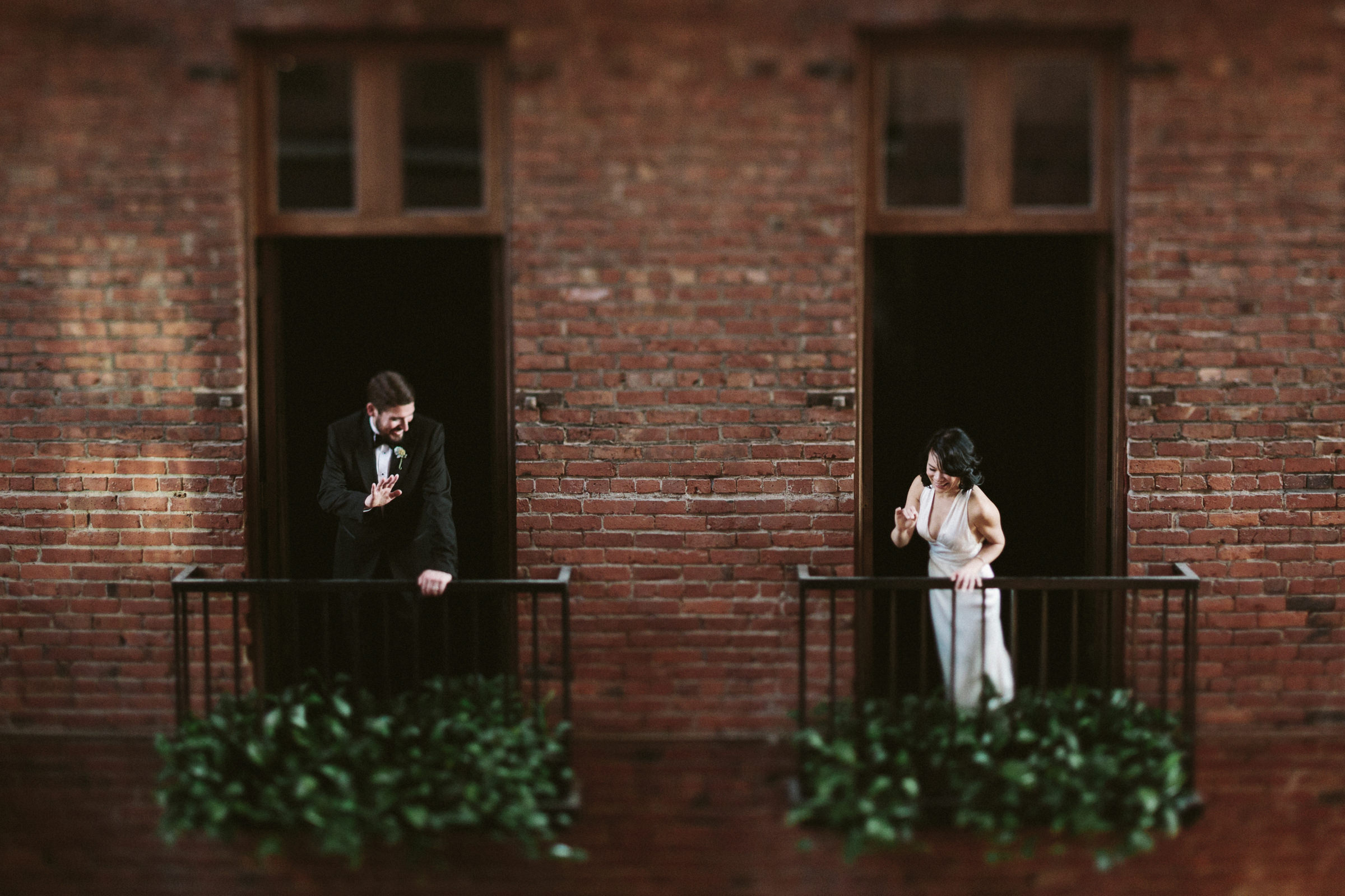Couple waving from separate balconies - photo by Jonas Seaman Photography