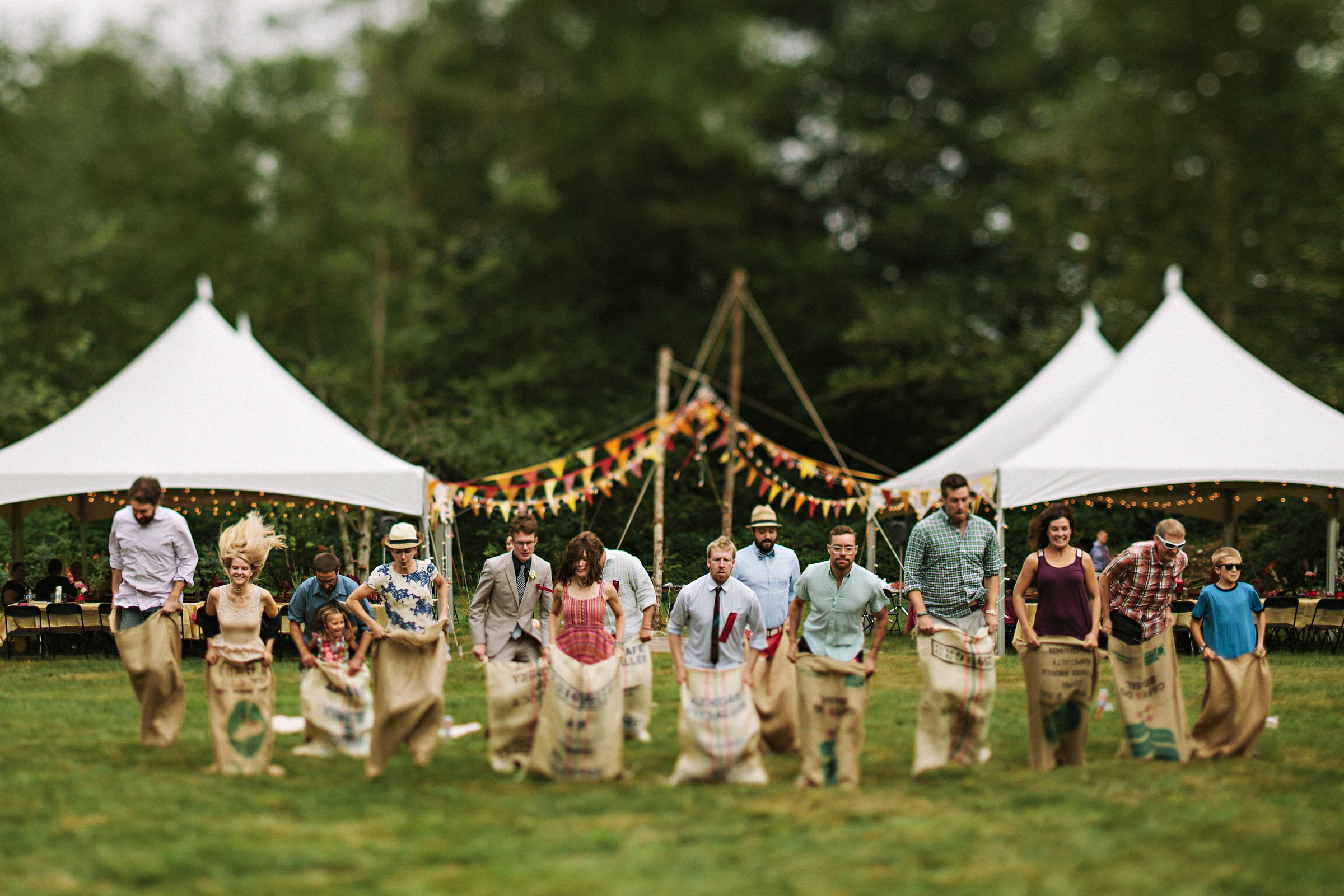 Fun group shot sack race amid outdoor tents and colorful bunting - photo by Jonas Seaman Photography
