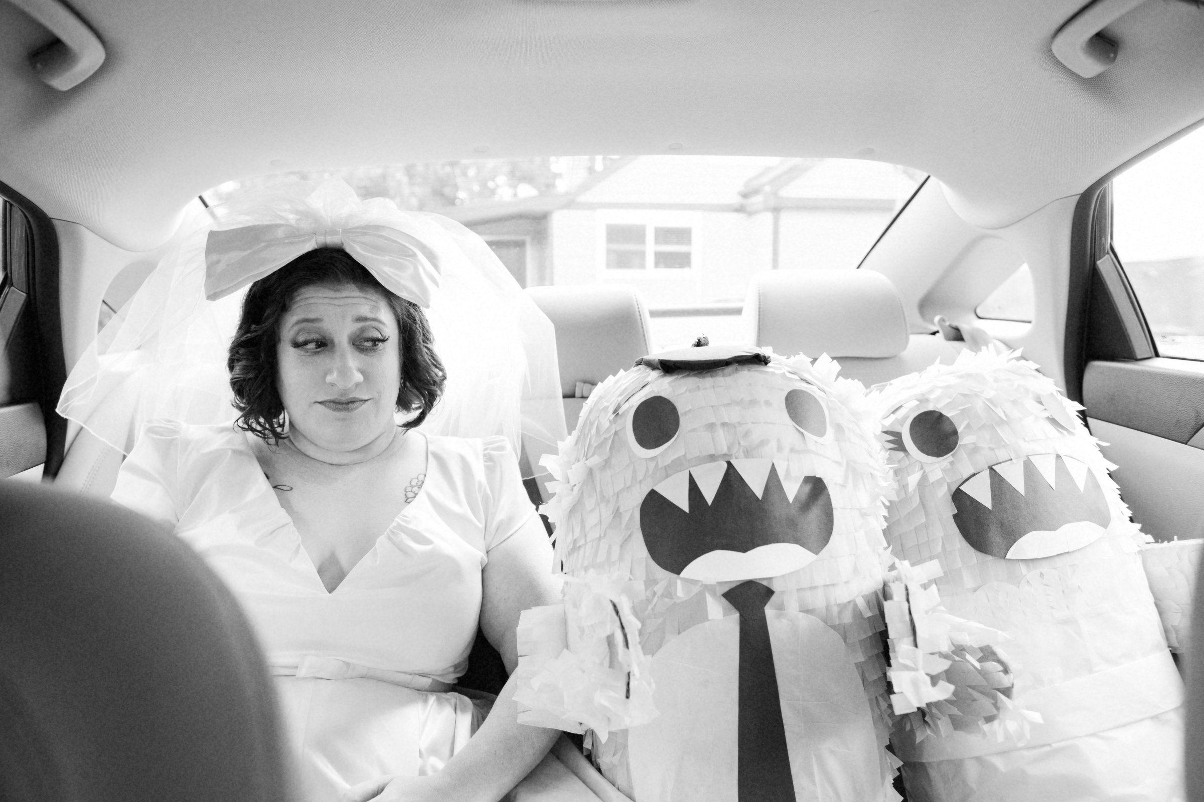 Funny portrait of bride in limo with bride and groom pinatas - photo by Jonas Seaman Photography