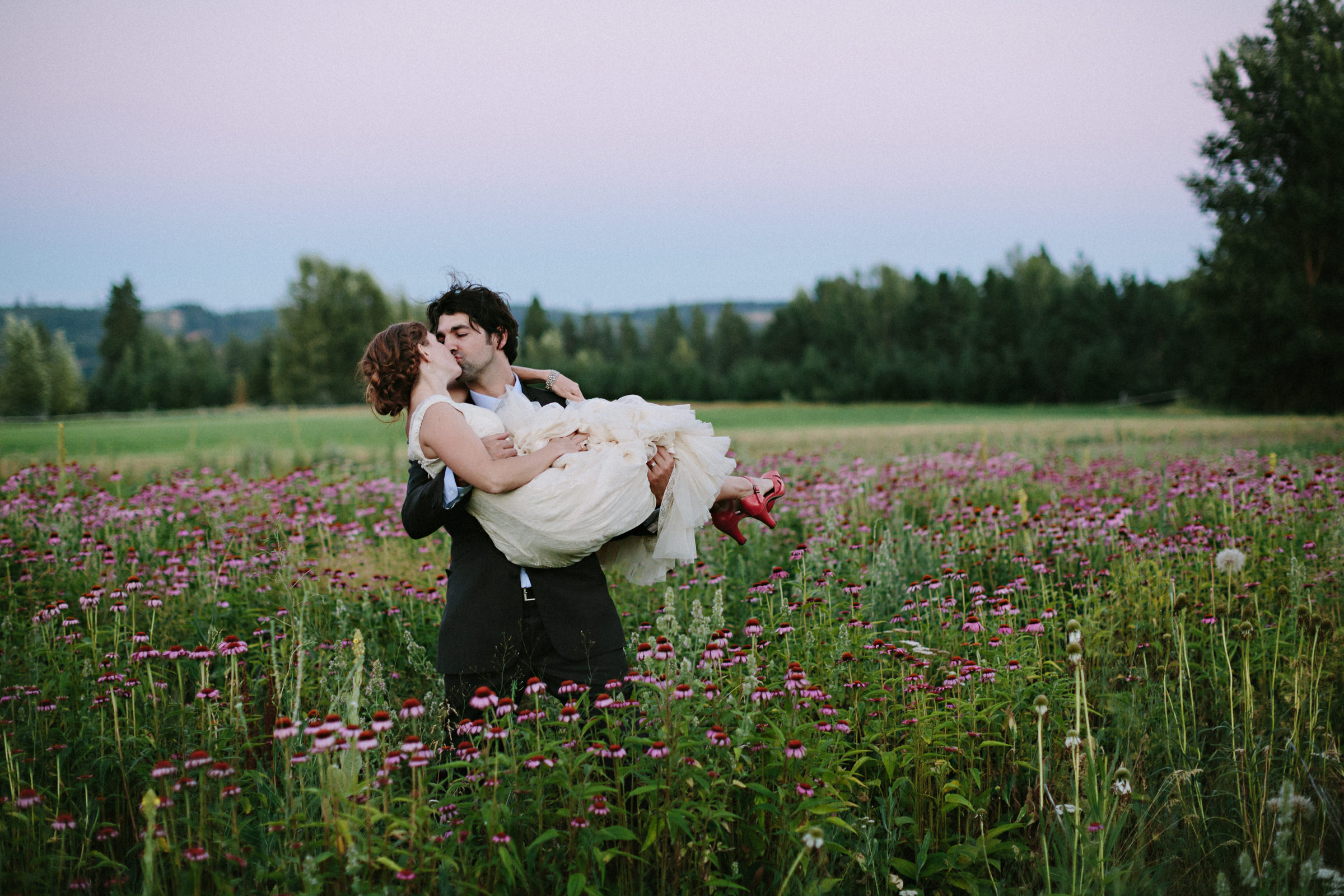 Groom carrying bride in field of flowers - photo by Jonas Seaman Photography