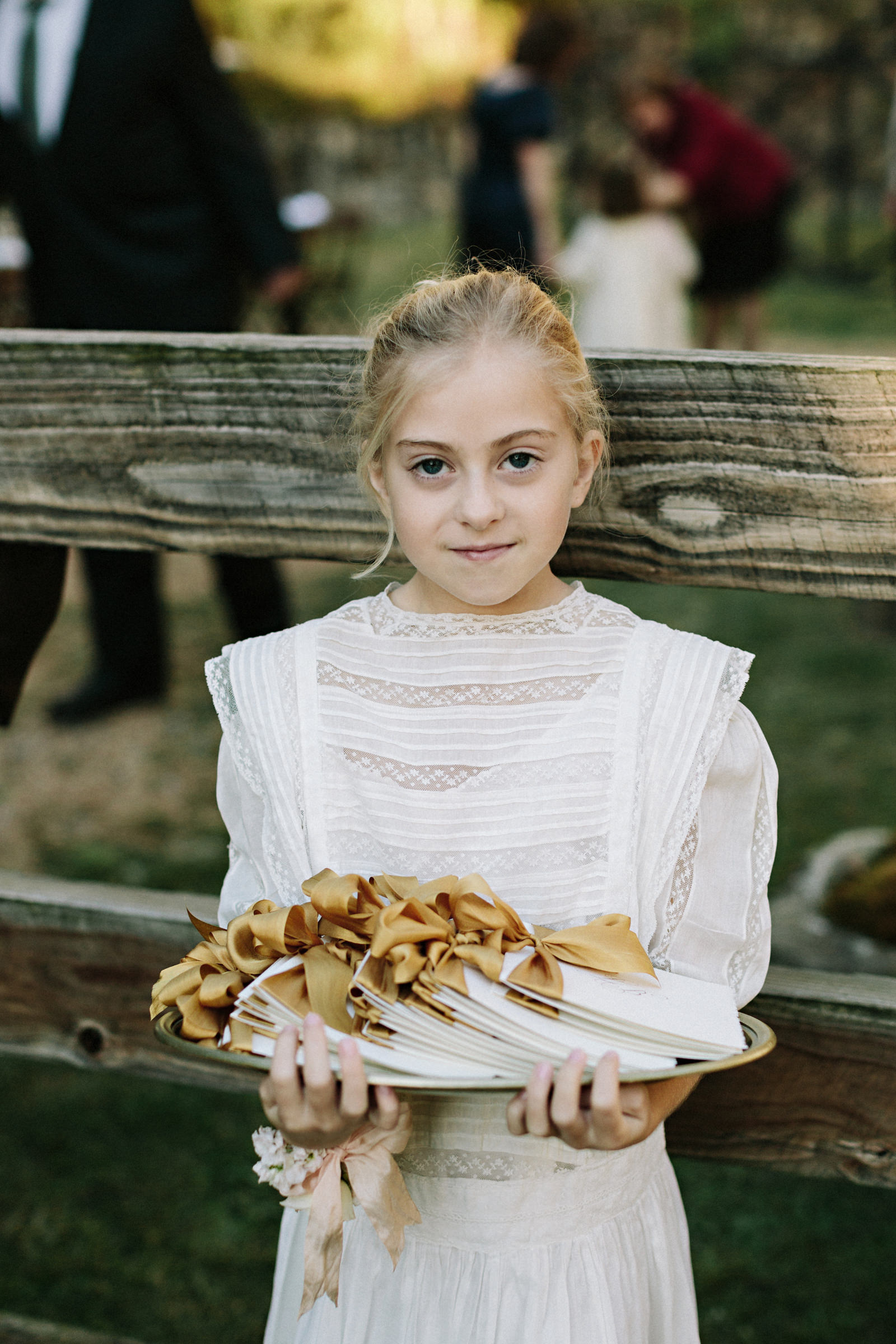 Portrait of girl in white lace holding tray of party favors- photo by Jonas Seaman Photography