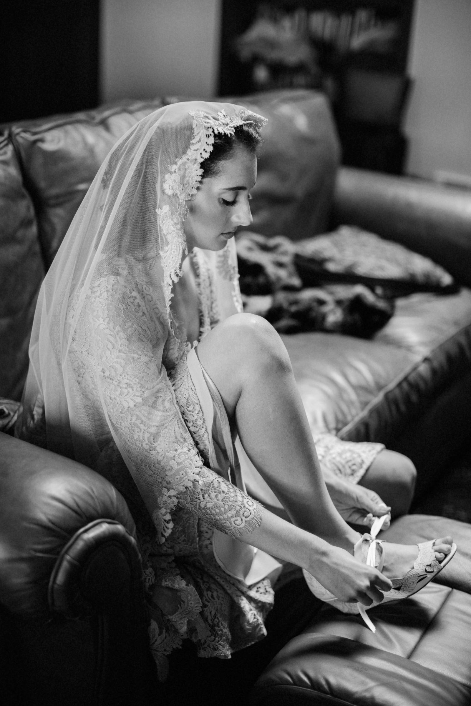 Seated veiled bride tying wedding shoes - photo by Jonas Seaman Photography