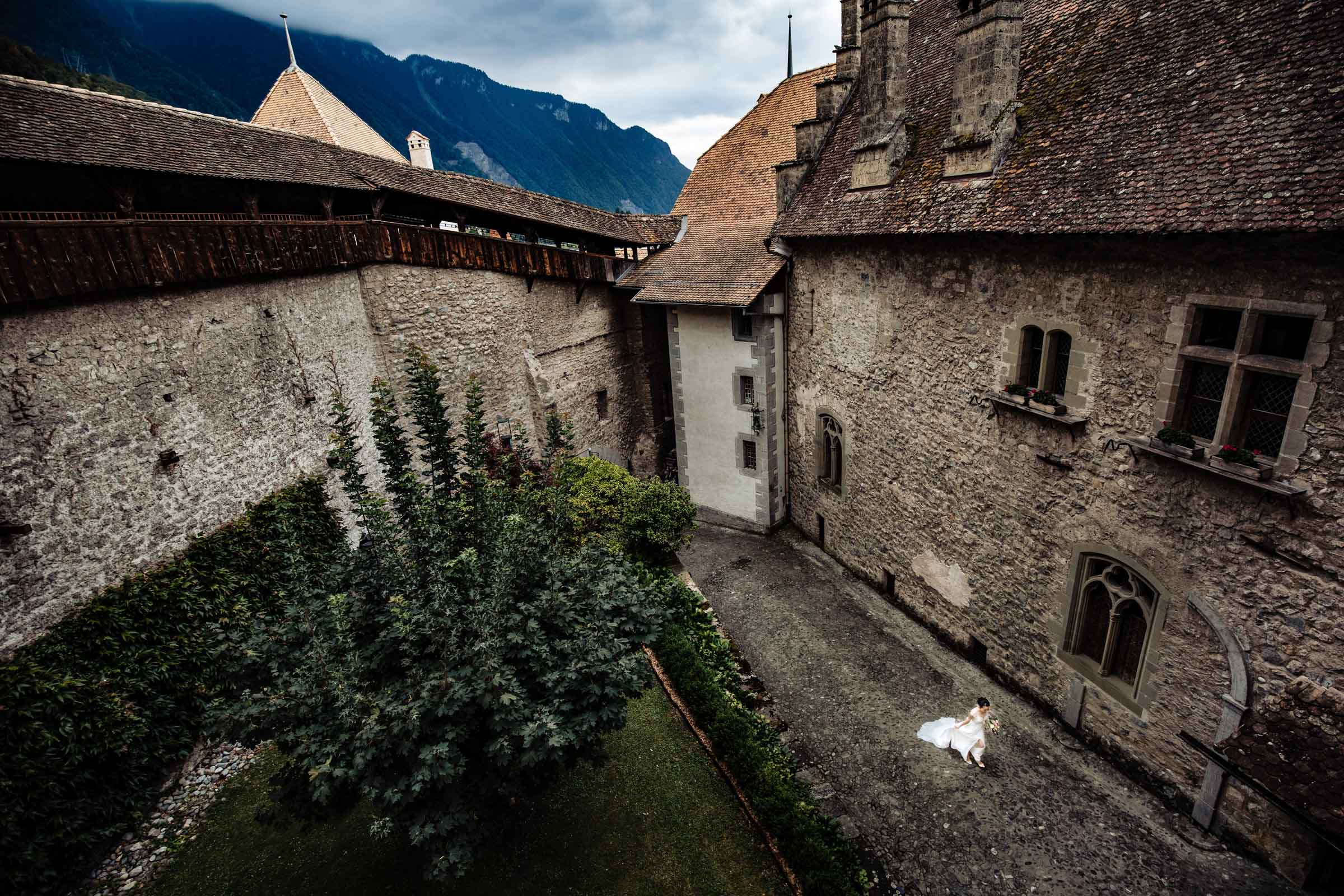 Aerial view of bride walking among historic rustic buildings - photo by Marissa Joy Photography