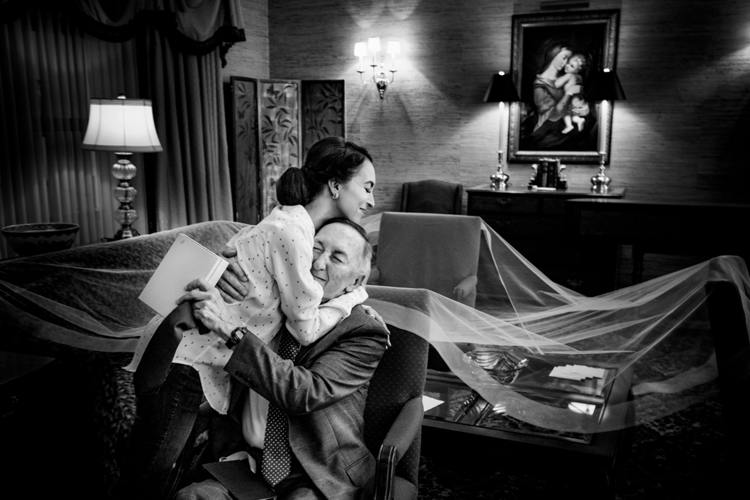 Bride hugs seated father - photo by Marissa Joy Photography