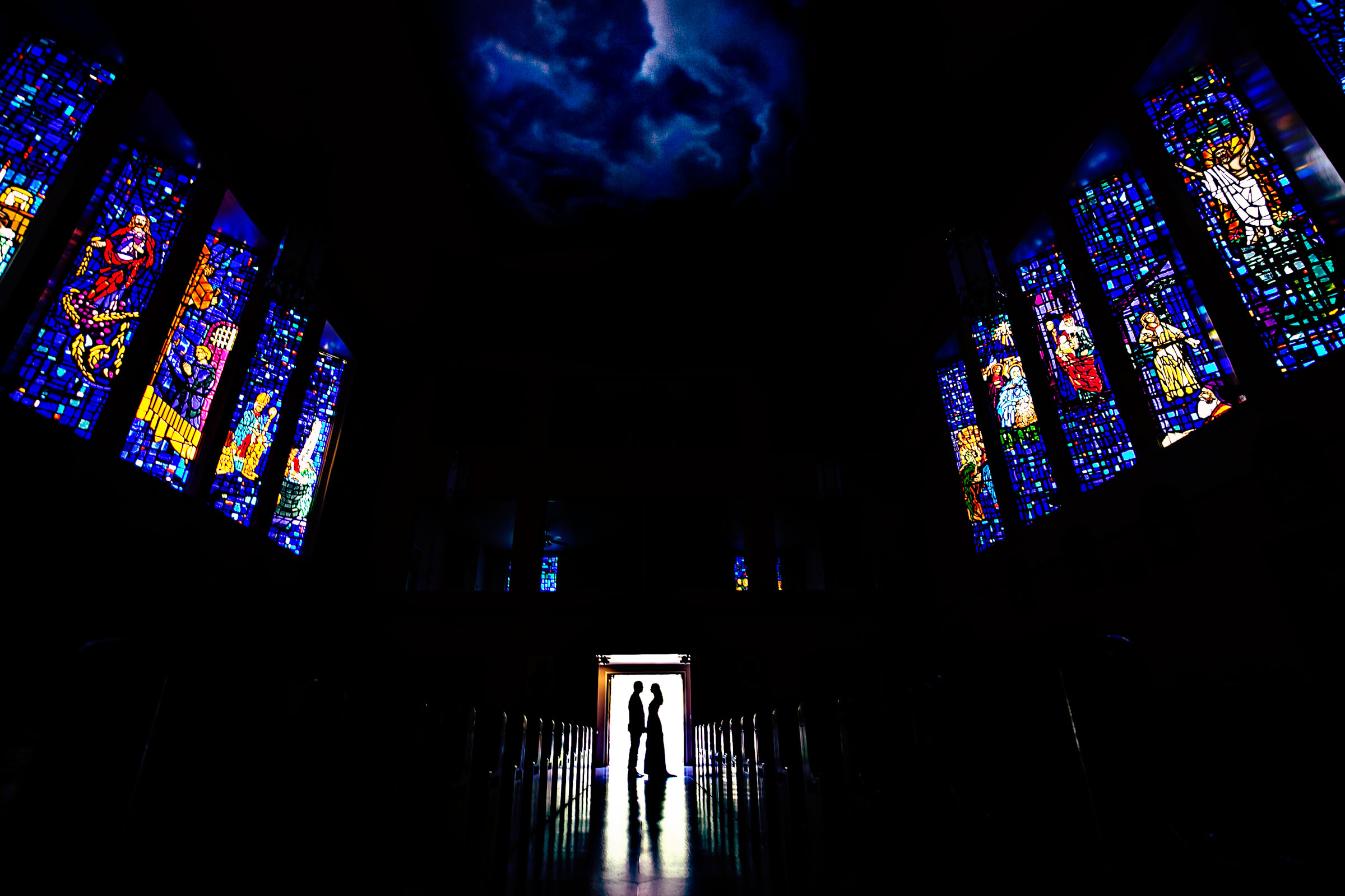 Couple silhouette with stained glass windows and nighttime sky - photo by Marissa Joy Photography