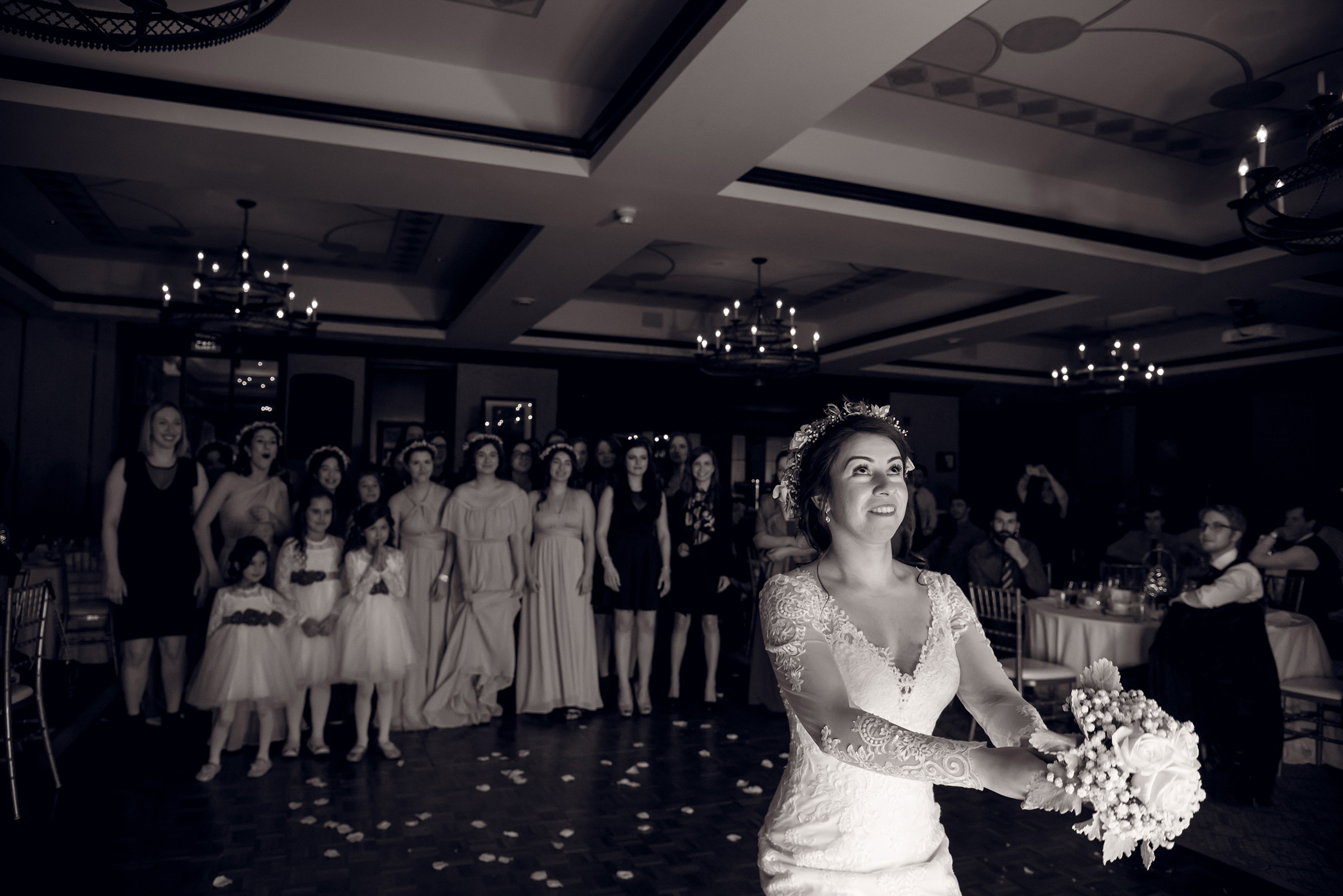 Black and white photo of bride tossing bouquet by David & Sherry Photography