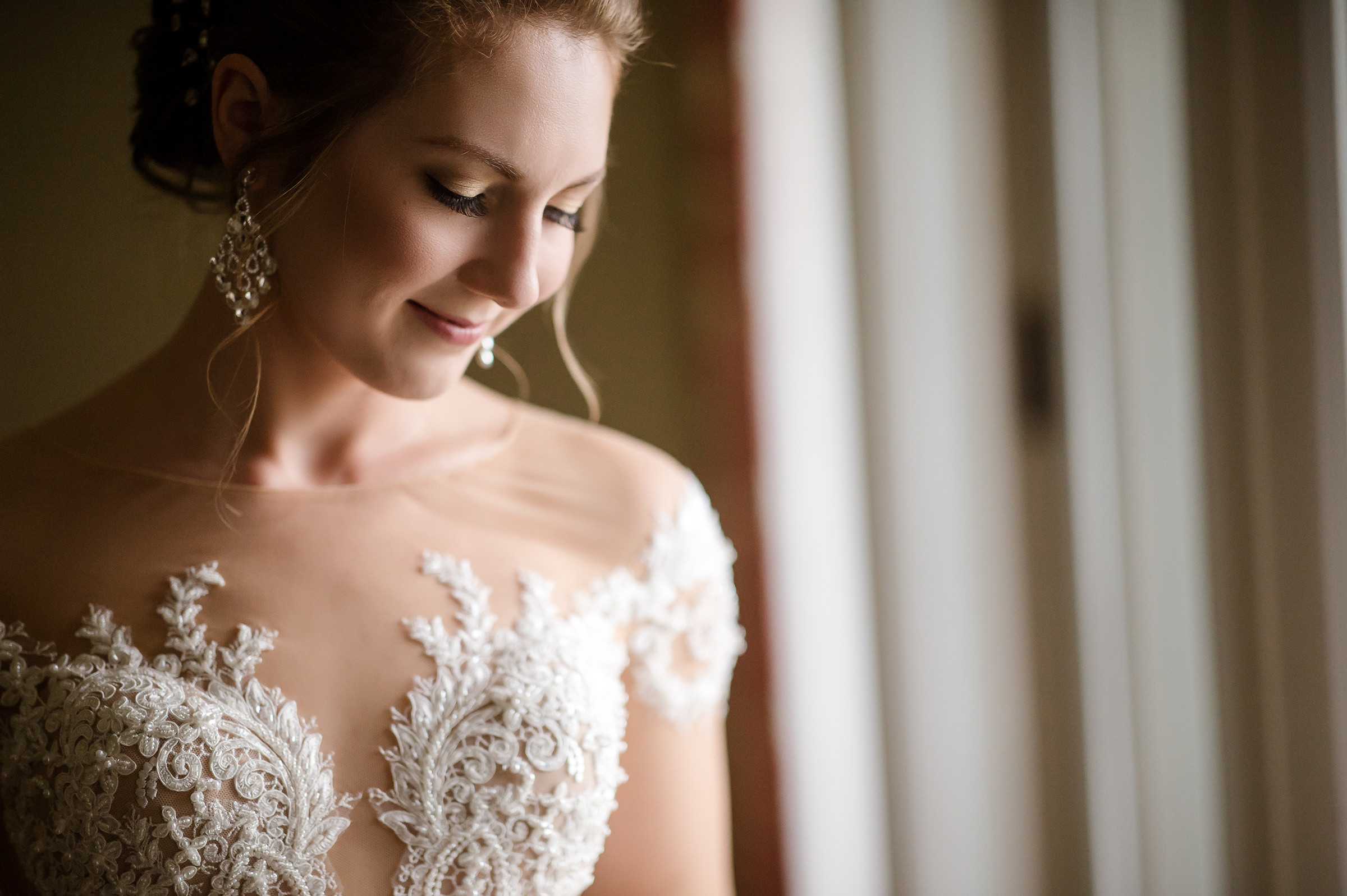 Bride wearing beaded applique bodice and chandelier earrings - photo by David & Sherry Photography