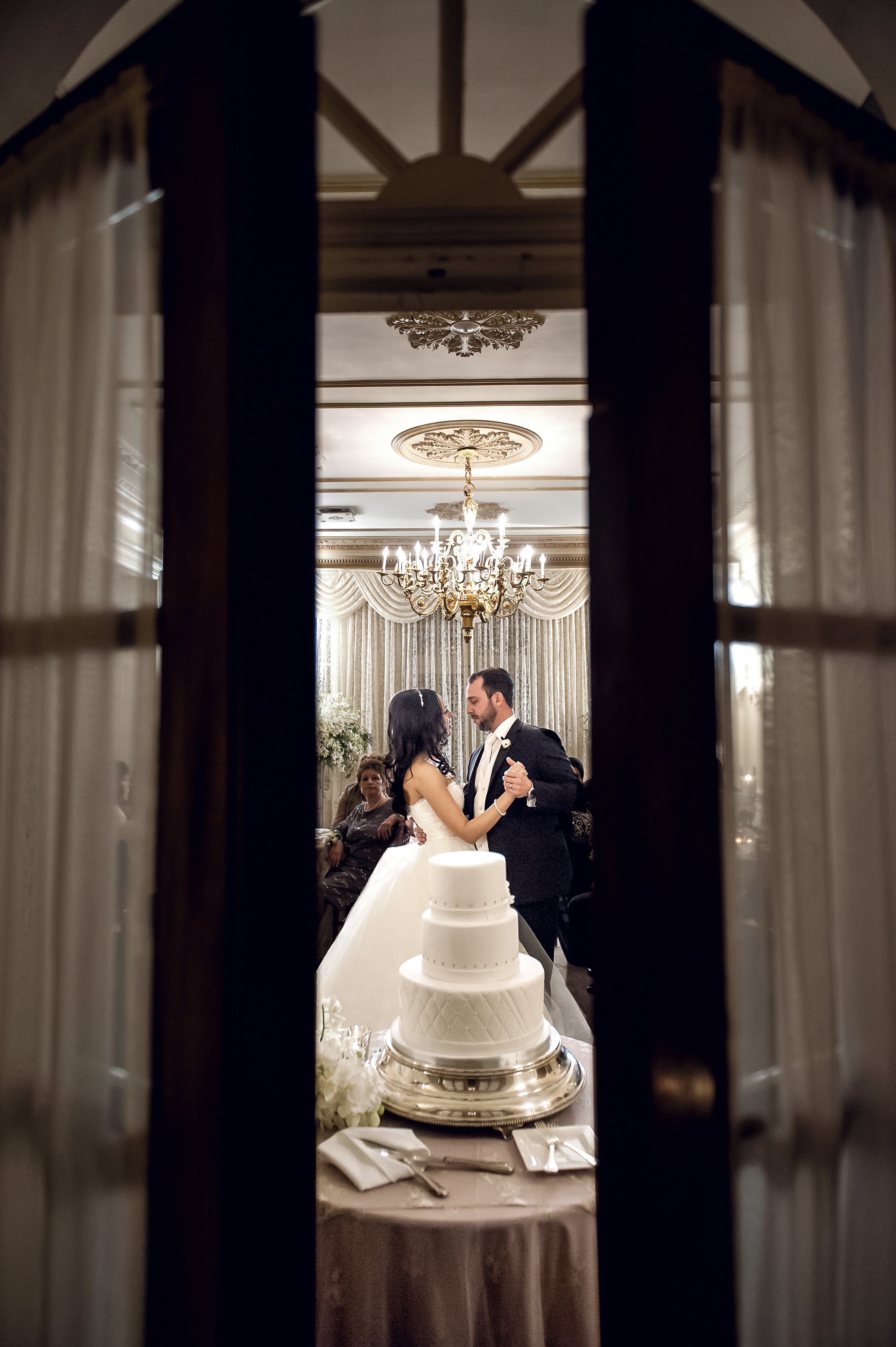 Graydon Hall couple dancing beyond curtain doors with cake in view - photo by David & Sherry Photography