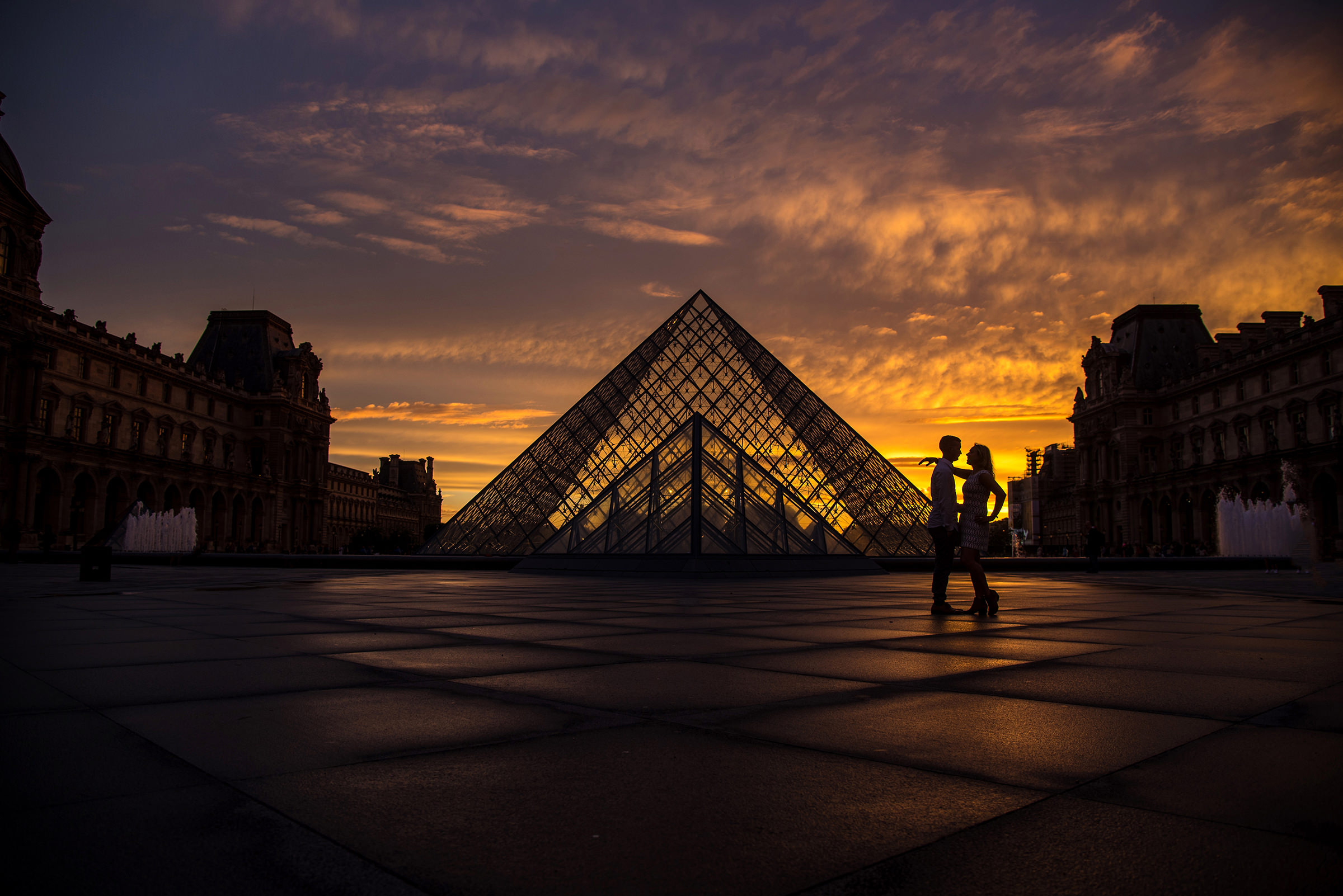 Engagement couple against Louvre at sunset - photo by David & Sherry Photography