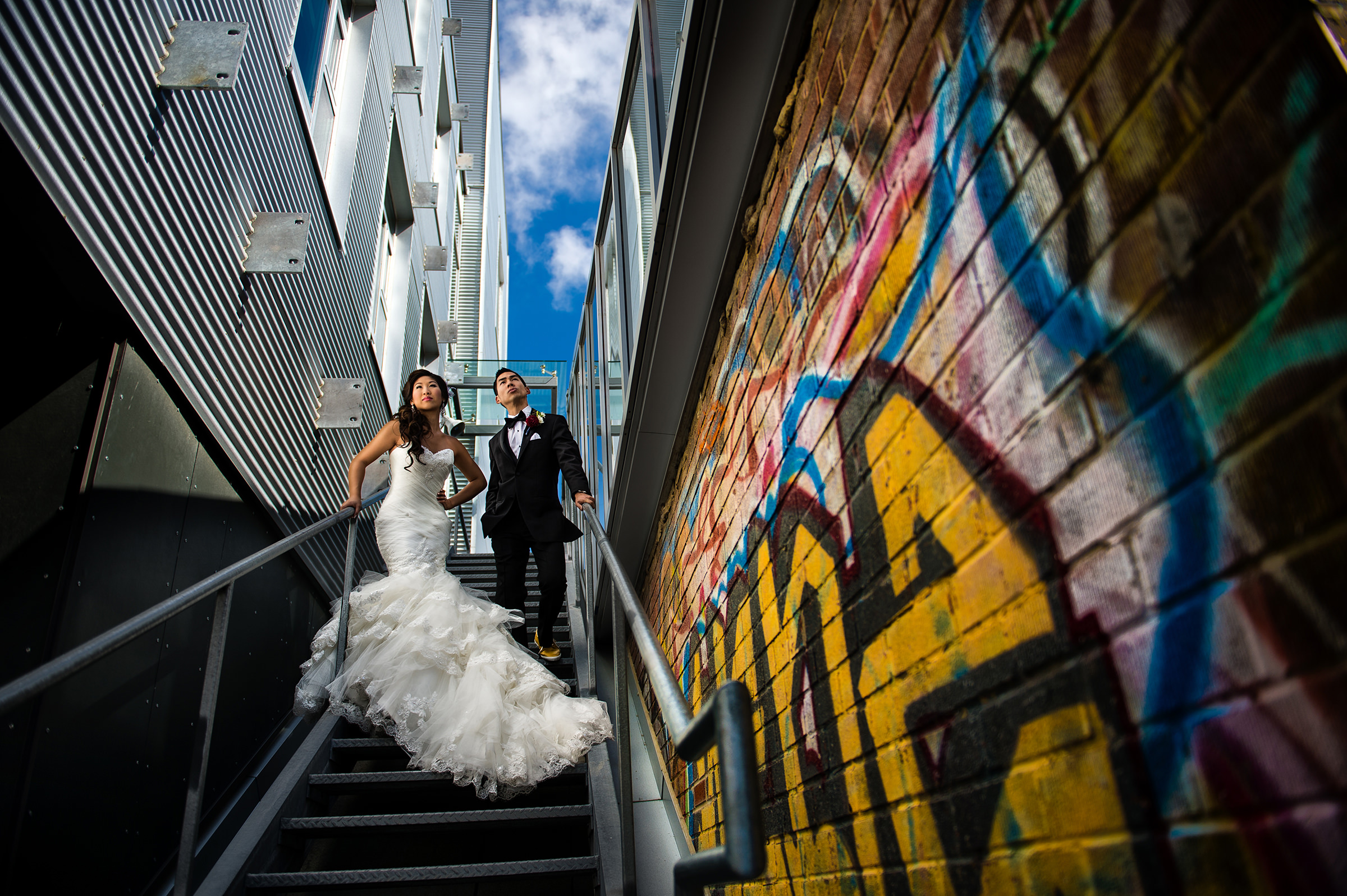 Urban wedding portrait with bride wearing trumpet ruffled dress by David & Sherry Photography