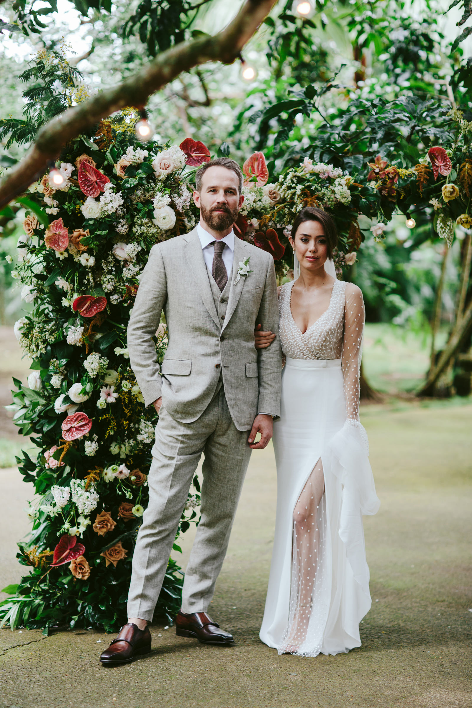 Bride and groom portrait in front of beautiful arbor - photo by Melia Lucida