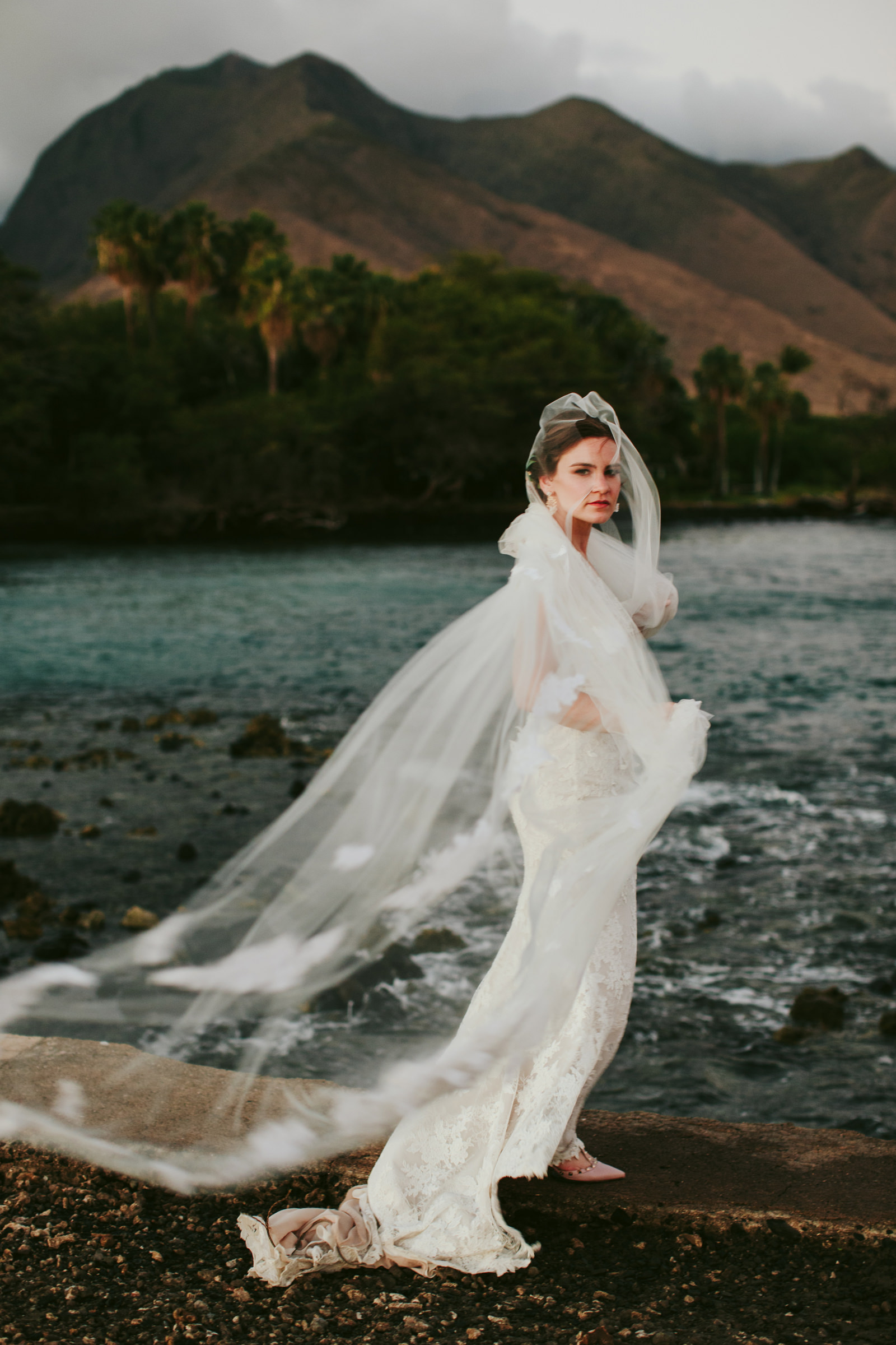 Bride at waters edge olowalu plantation house maui - photo by Melia Lucida