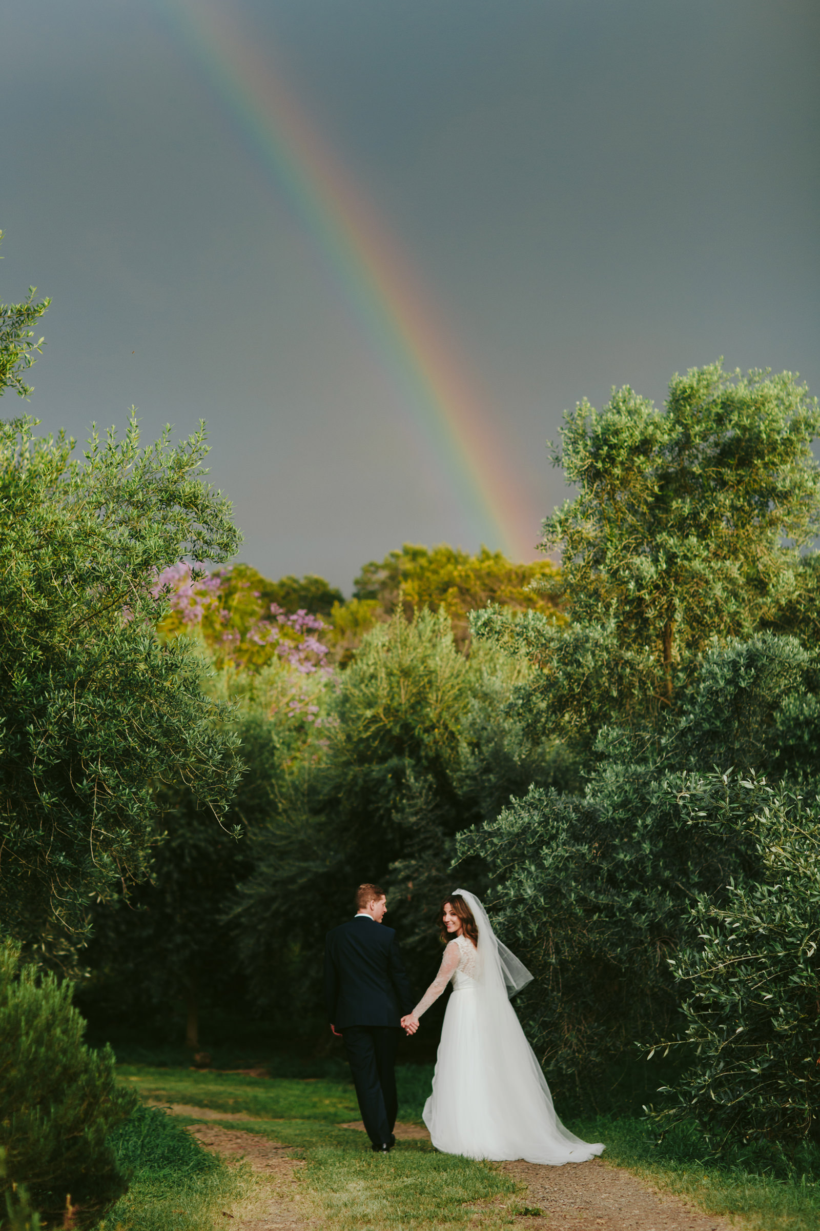 Calasa olive farm maui couple walks down path under rainbow - photo by Melia Lucida