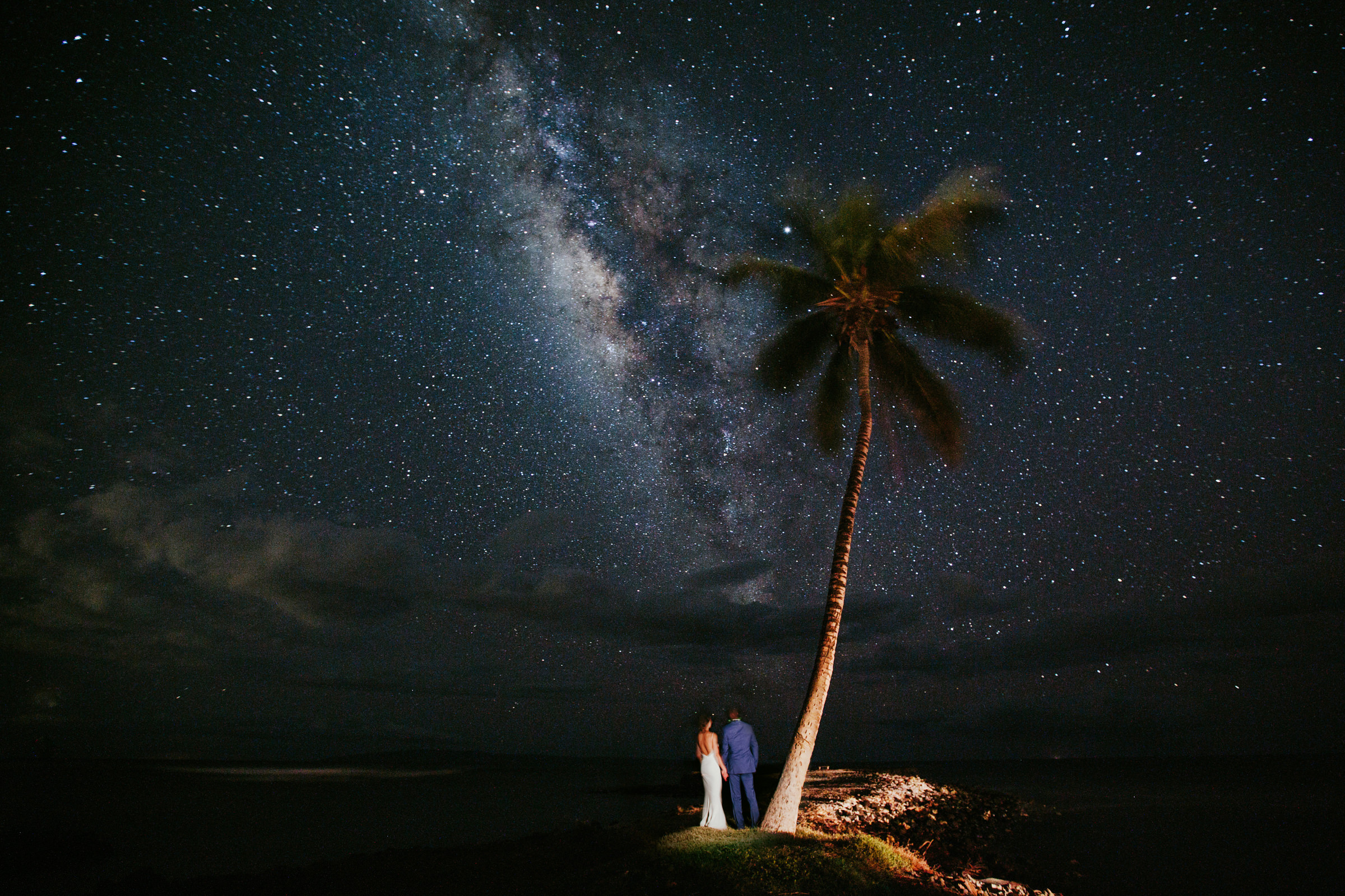 Couple stands under the Milky Way - photo by Melia Lucida