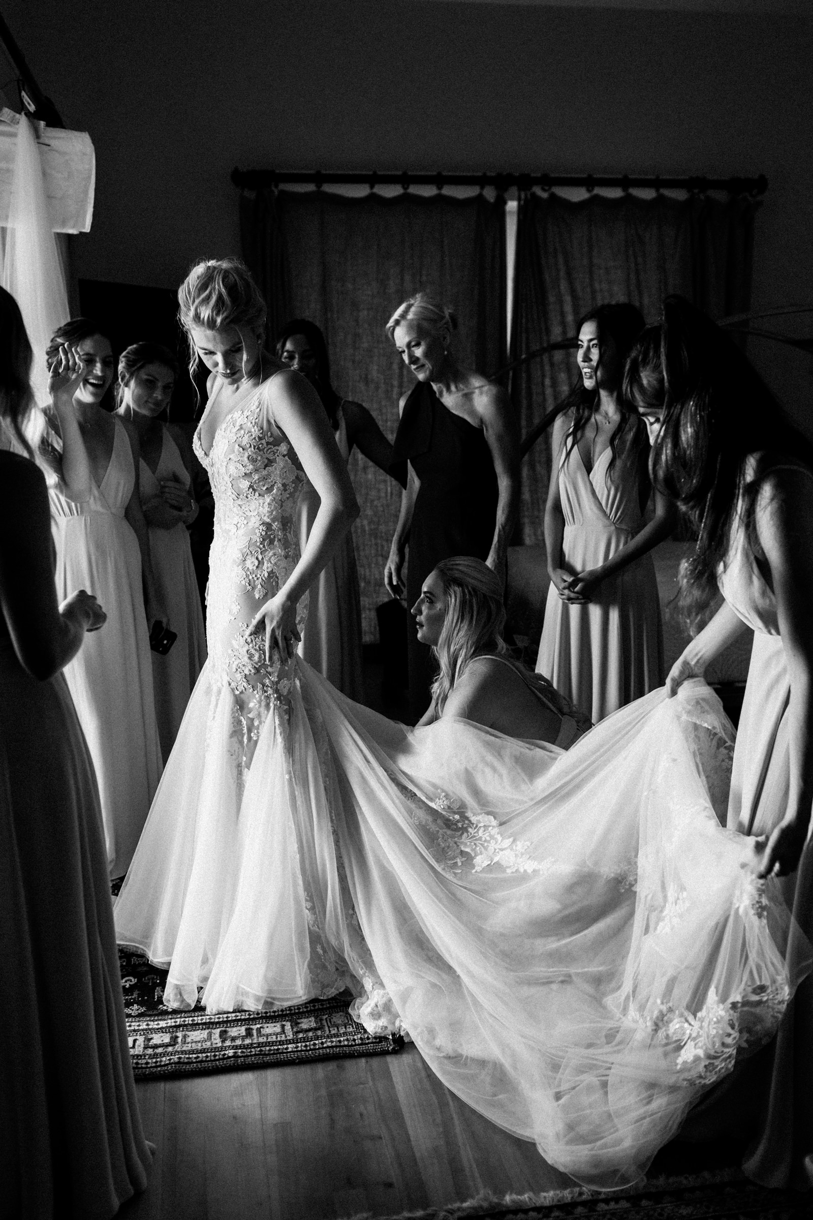 Glamorous bride finishing touches on gown - photo by Melia Lucida