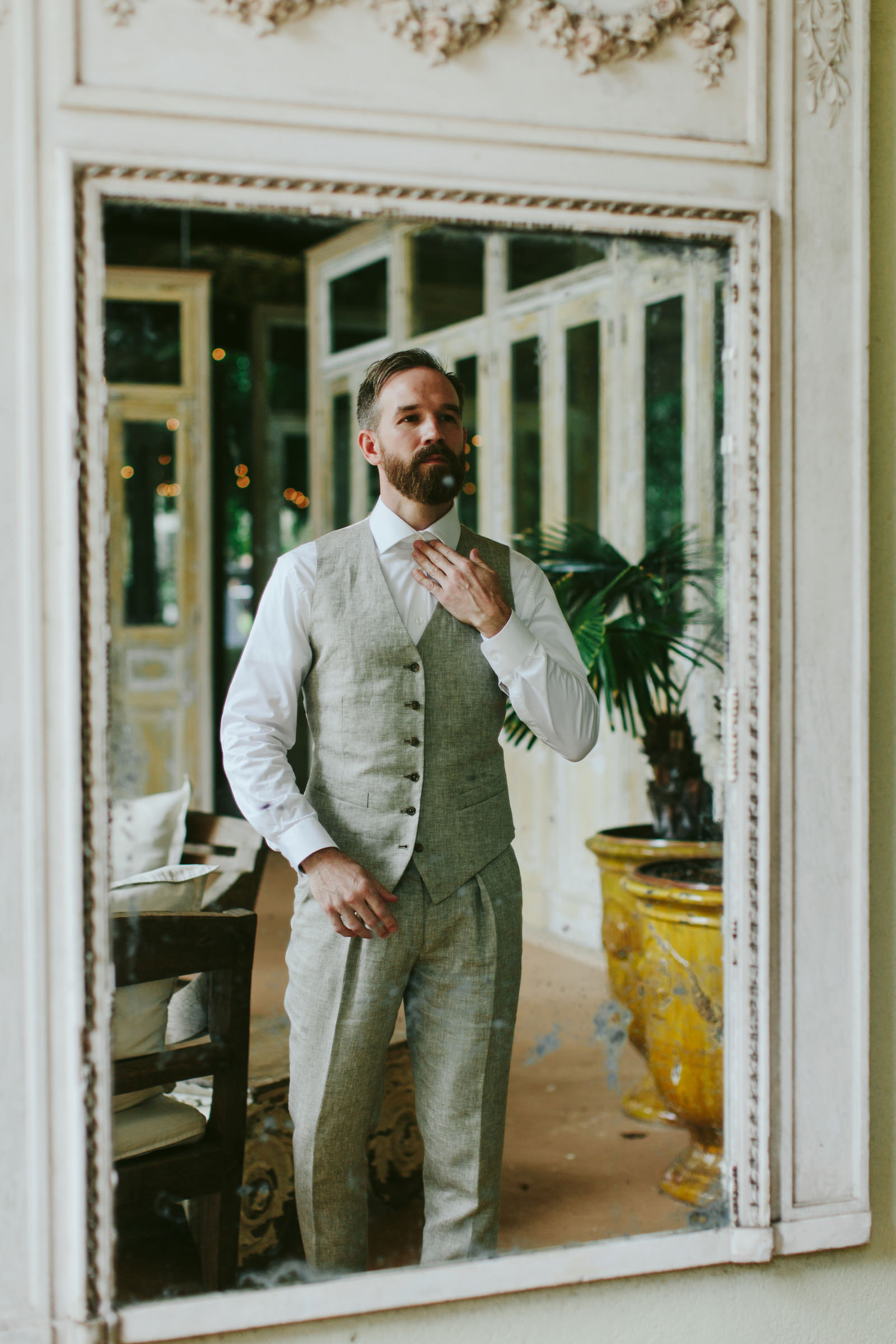 Groom gets dressed in front of mirror - photo by Melia Lucida