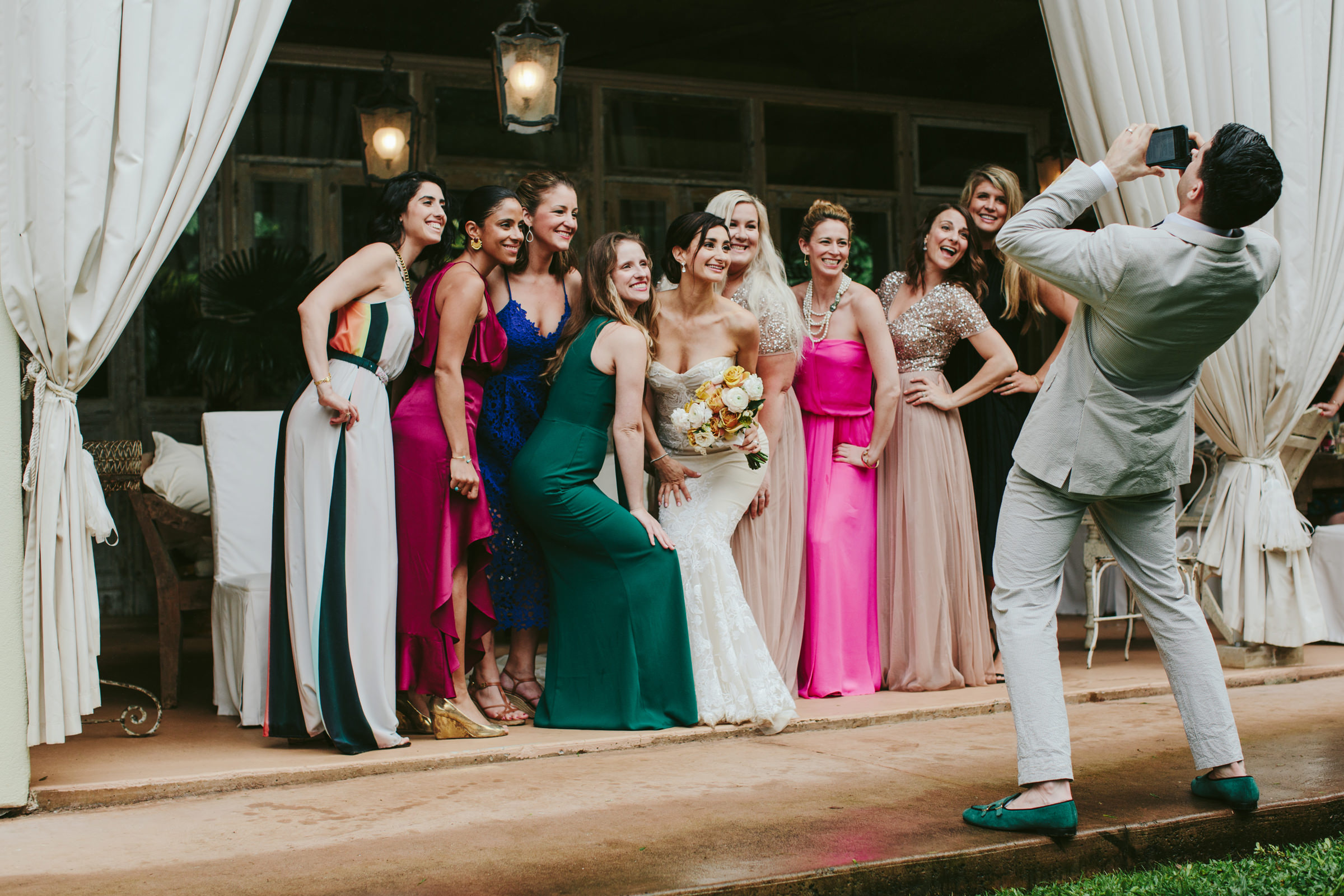 Groom leans back to take photo of bridal party - photo by Melia Lucida