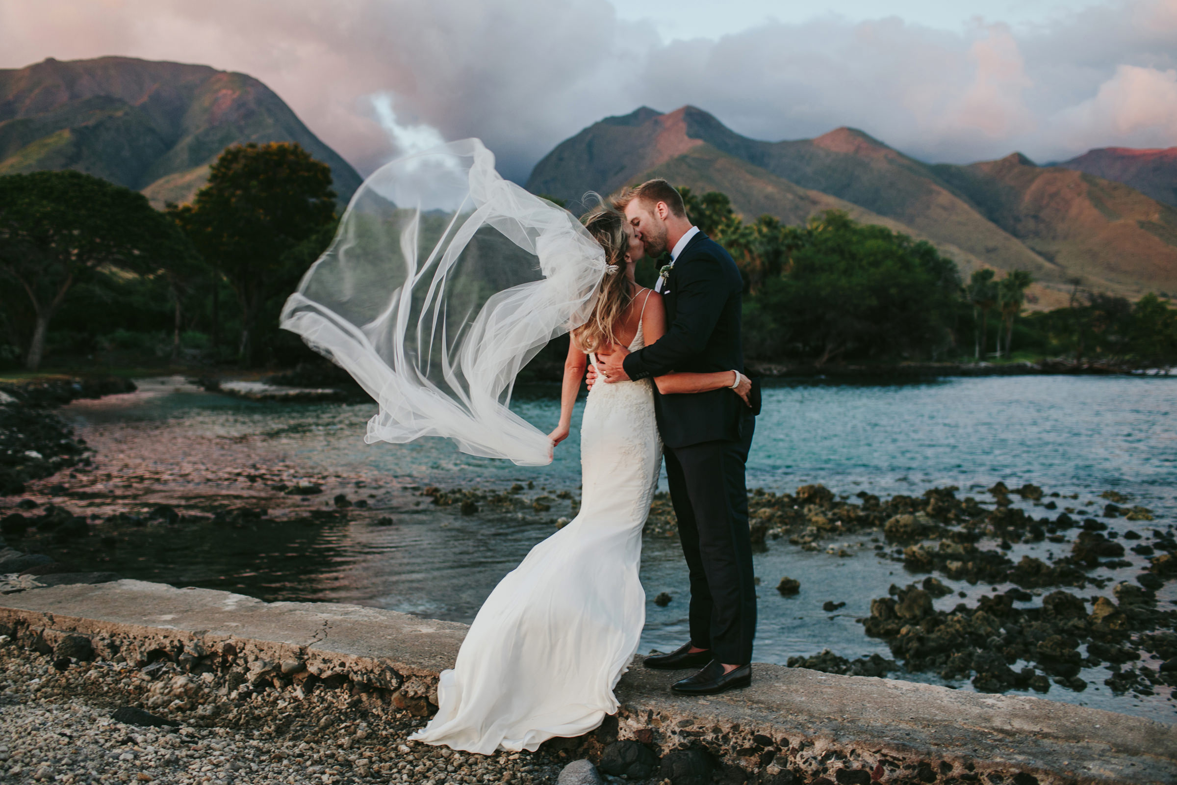 Maui beachfront photo of couple embracing with veil blowing - photo by Melia Lucida