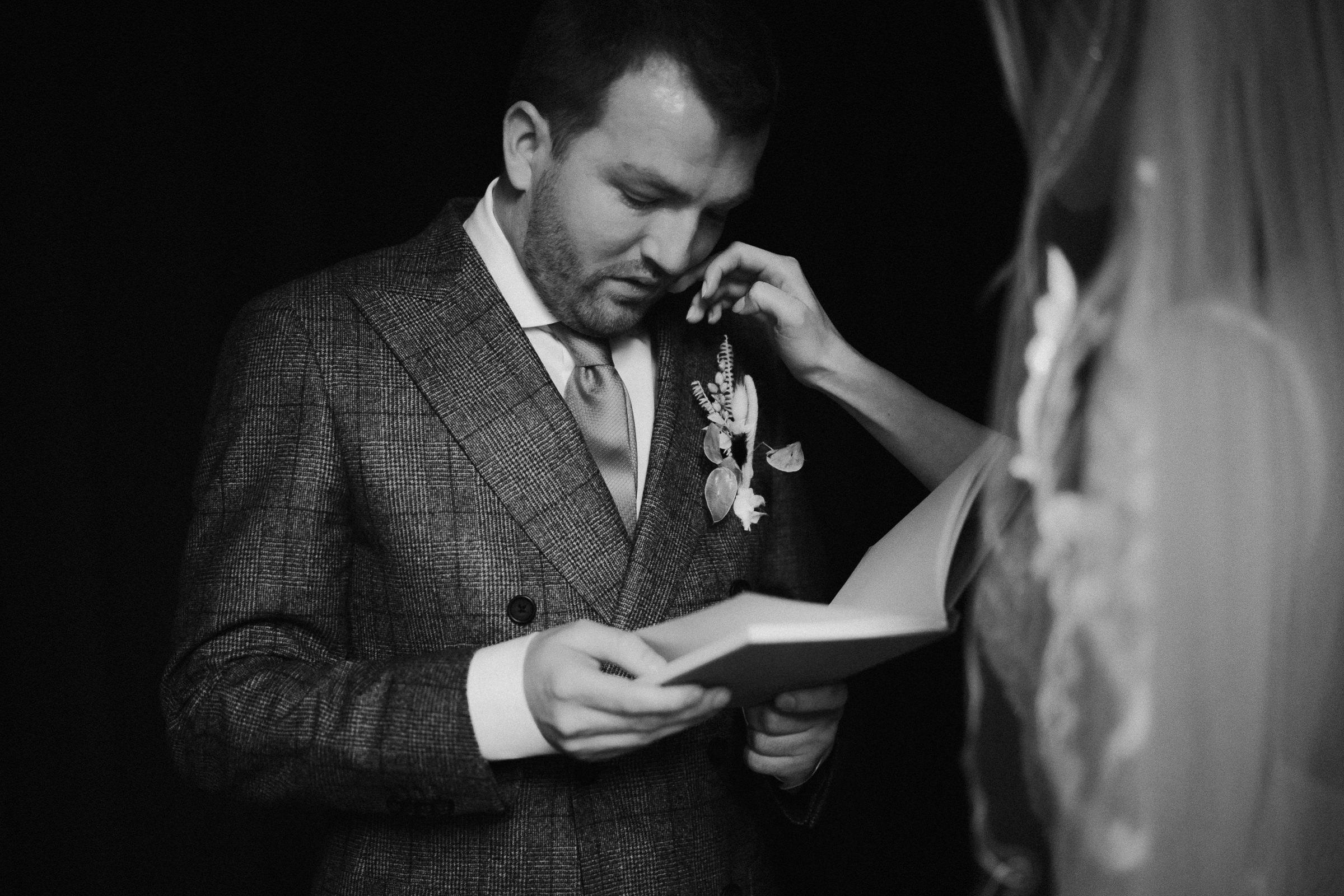Bride wipes tear from groom's face as he reads - photo by Naomi van der Kraan
