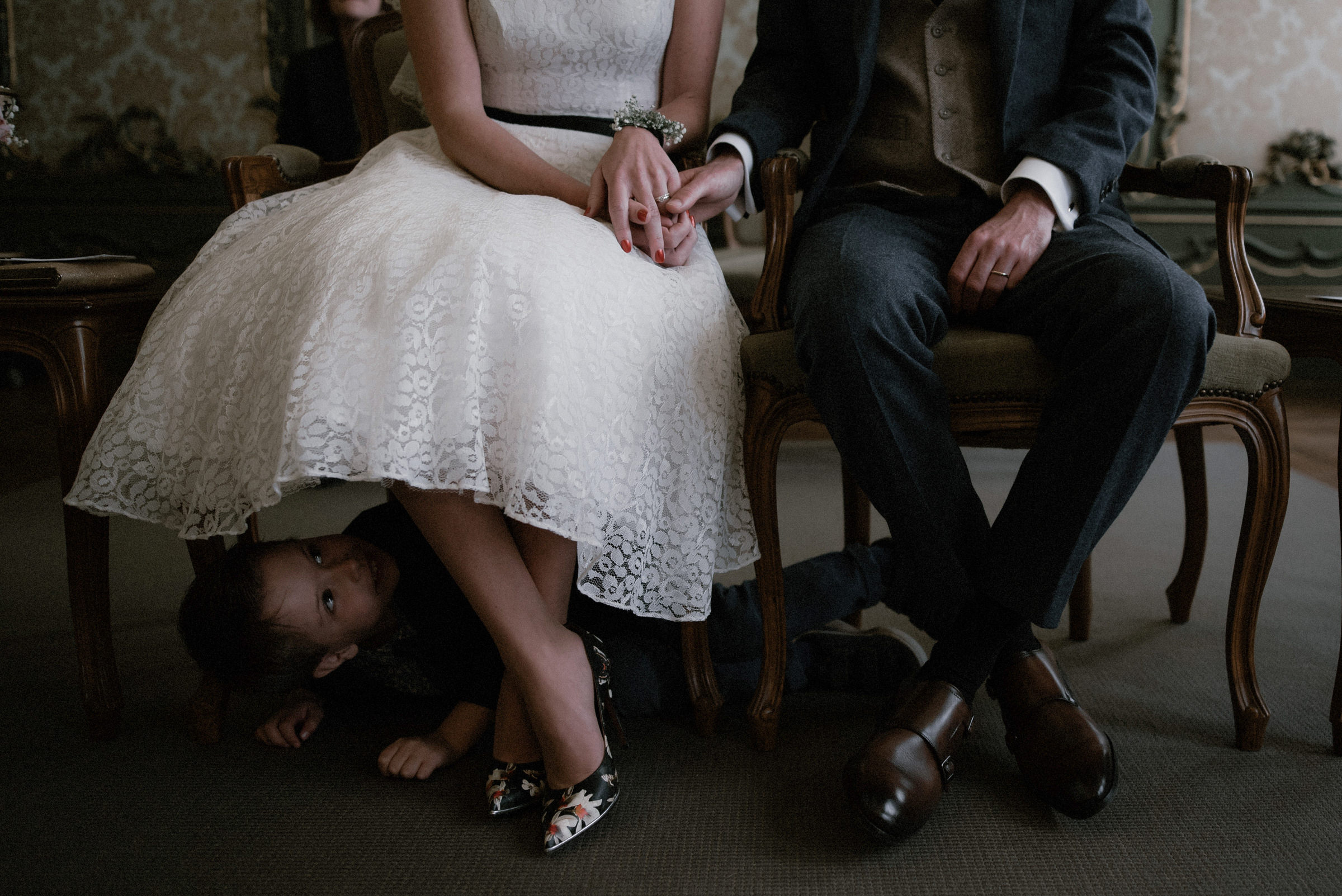 Little boy looks up dress of seated bride - photo by Naomi van der Kraan