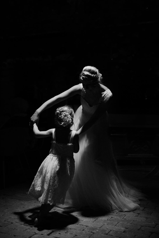 Low light portrait of bride and little girl dancing - photo by Naomi van der Kraan
