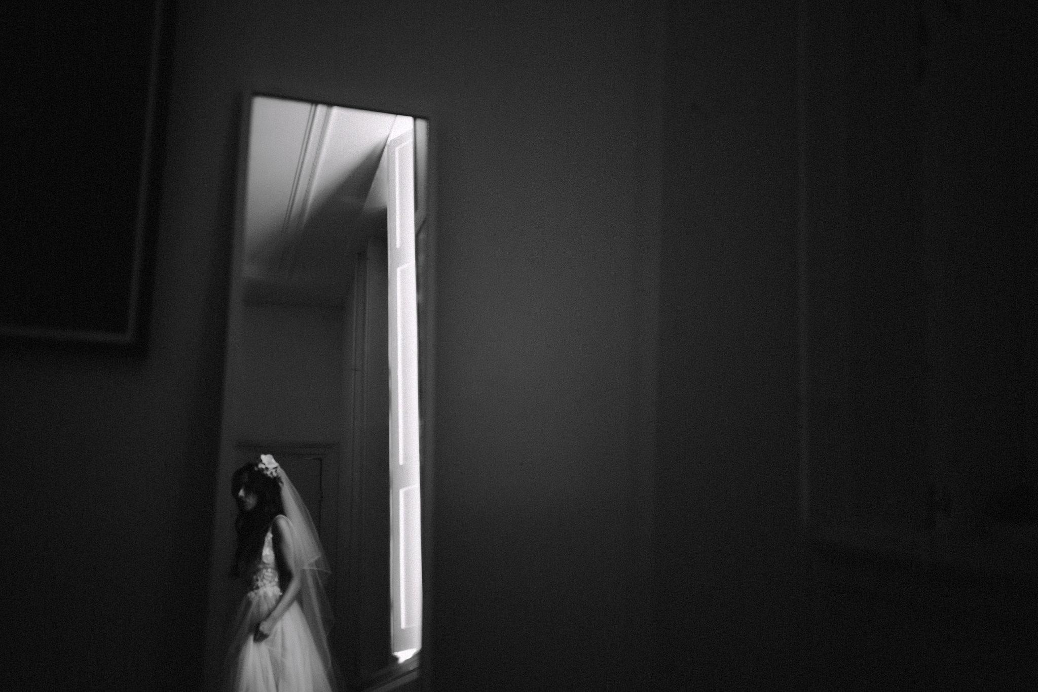 Bride seen through her bedroom door by window - photo by Naomi van der Kraan