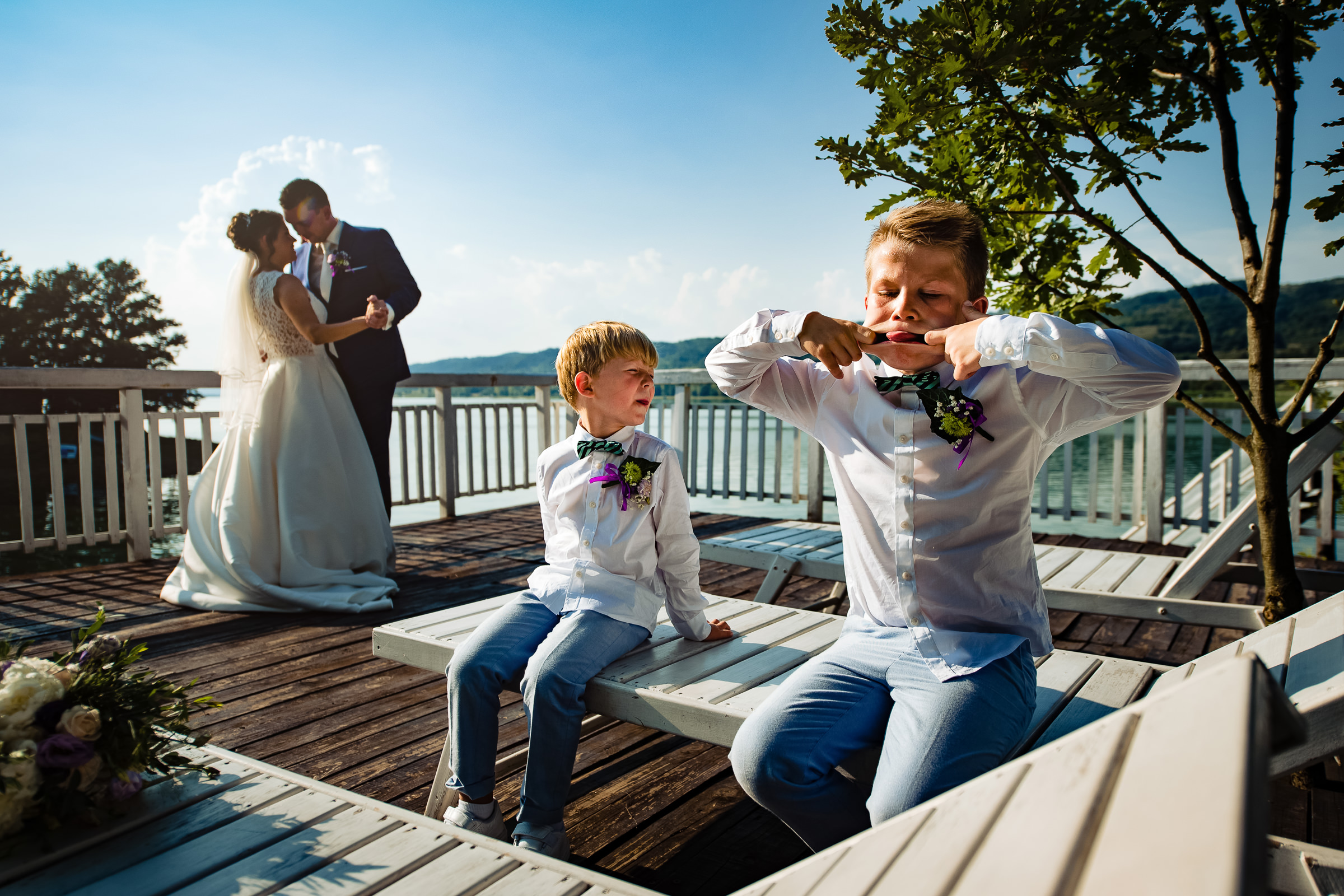 Boy makes funny face while couple embraces on waterfront dock - photo by Deliysky Studio