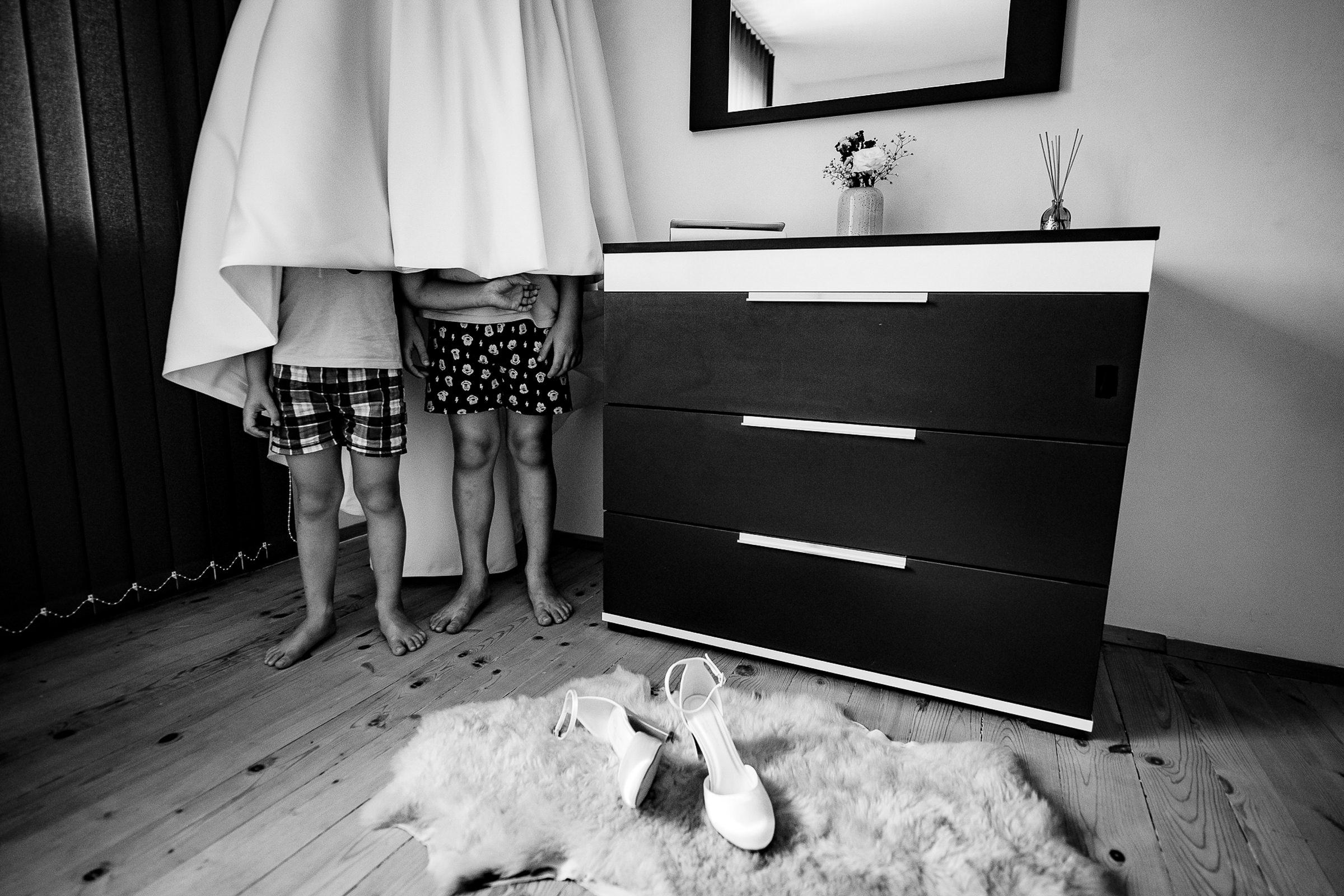 Boys hiding under hanging gown - photo by Deliysky Studio