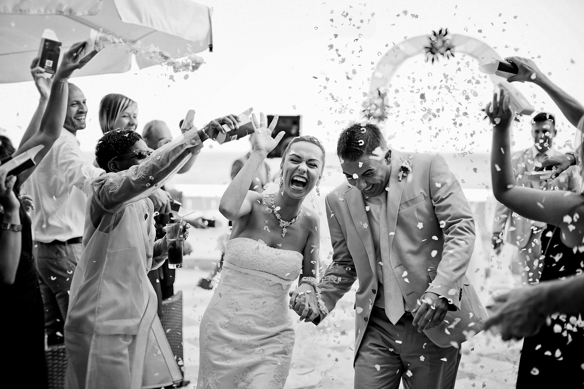 Bride and groom showered with flower petals - black and white photo by Deliysky Studio