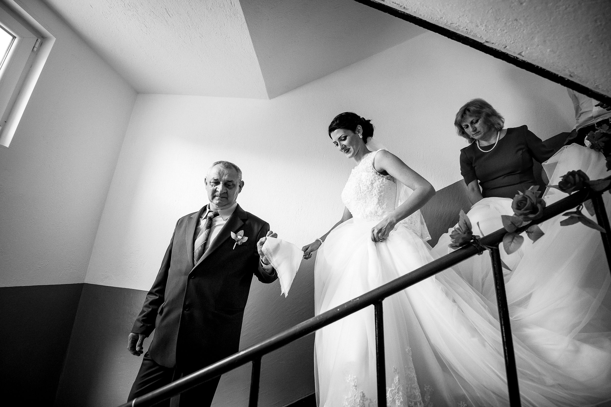 Bride descends stairs with mother and father - photo by Deliysky Studio