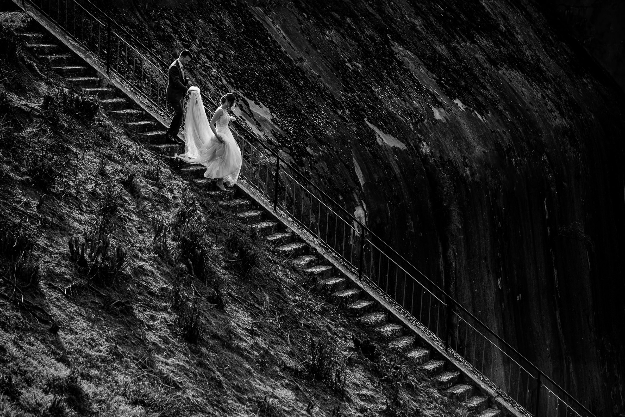 Bride descends steep cliff stairs while groom holds her gown - photo by Deliysky Studio