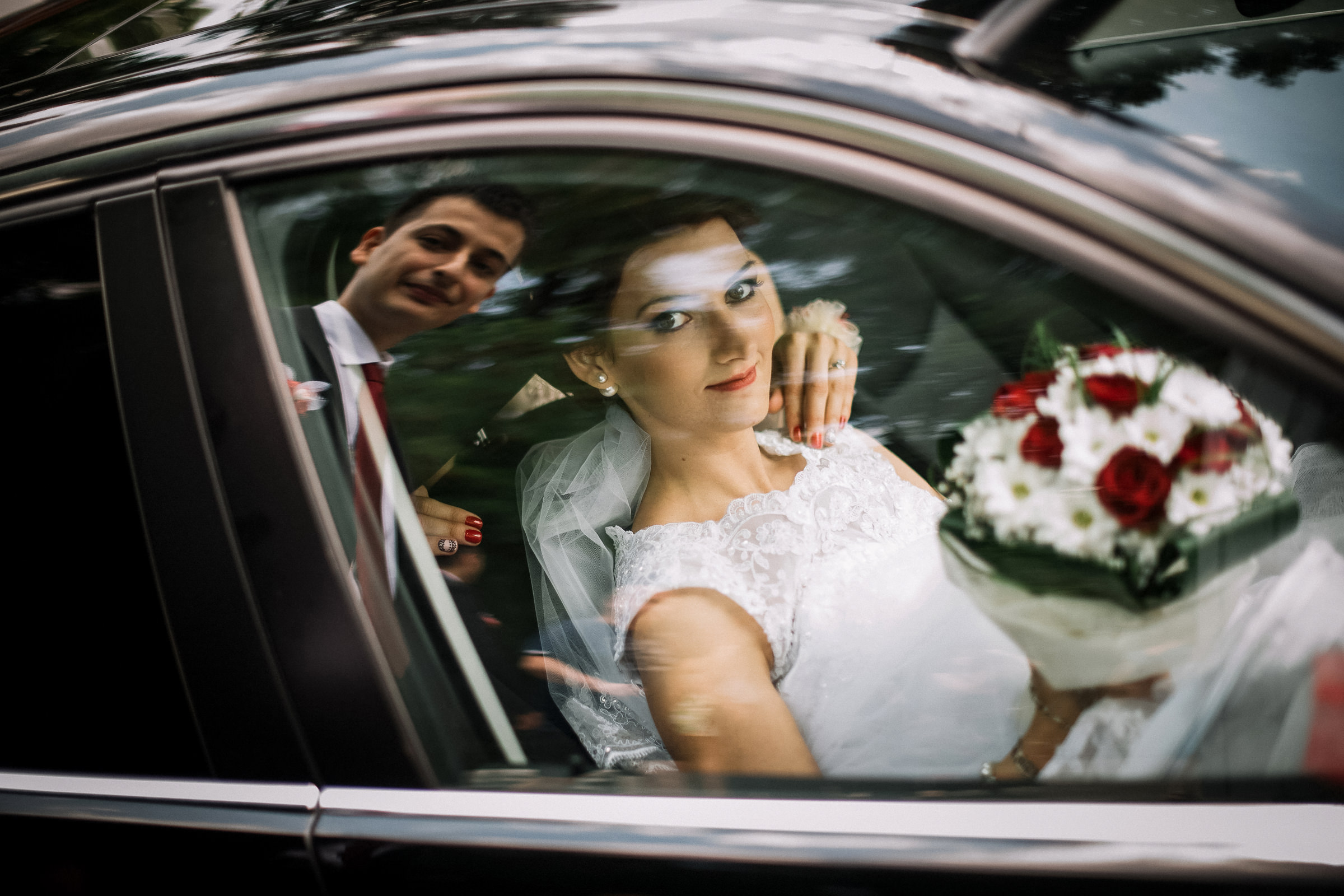 Bride in limo with groom reflected - photo by Deliysky Studio