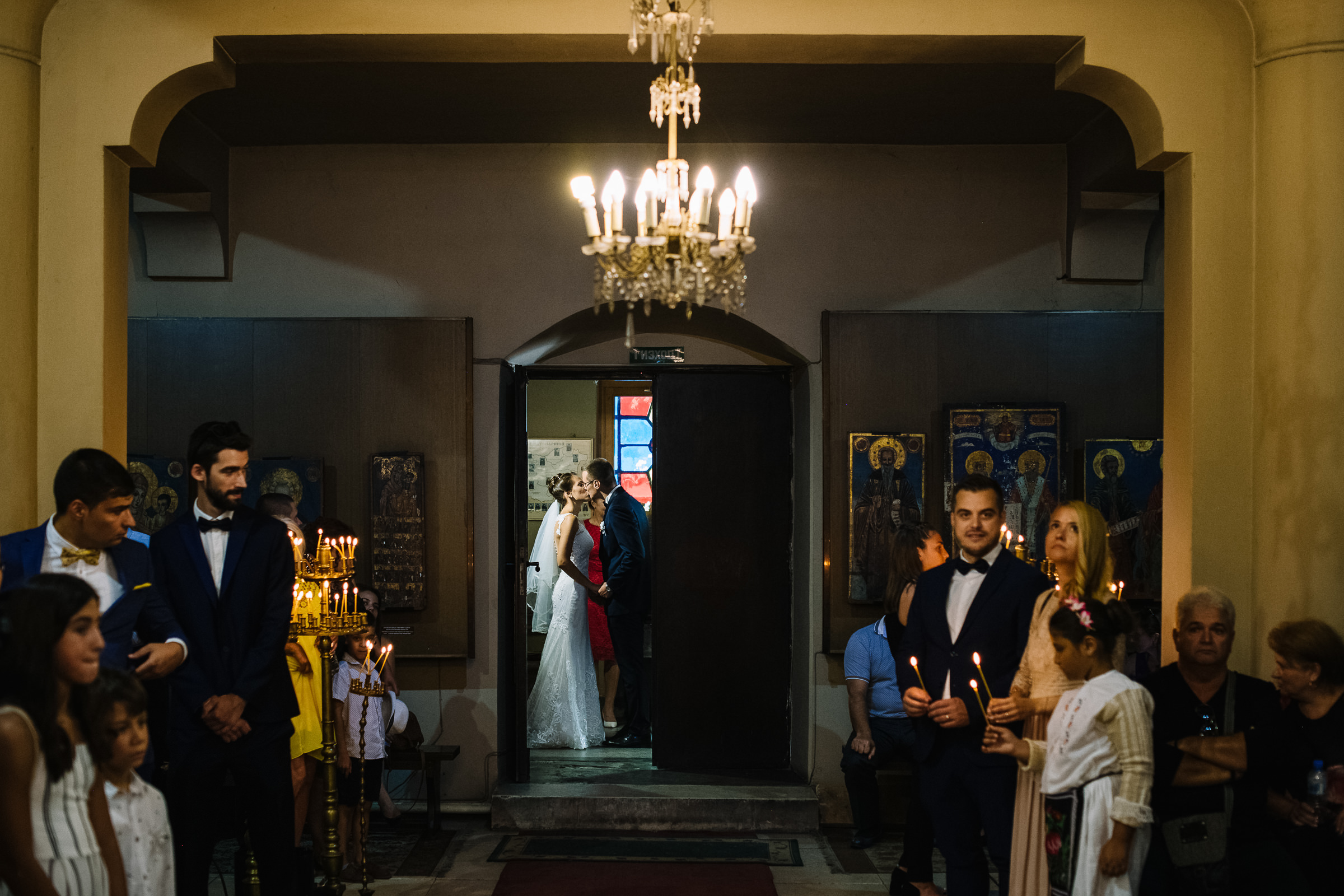 Couple sneaks a kiss before processional - photo by Deliysky Studio