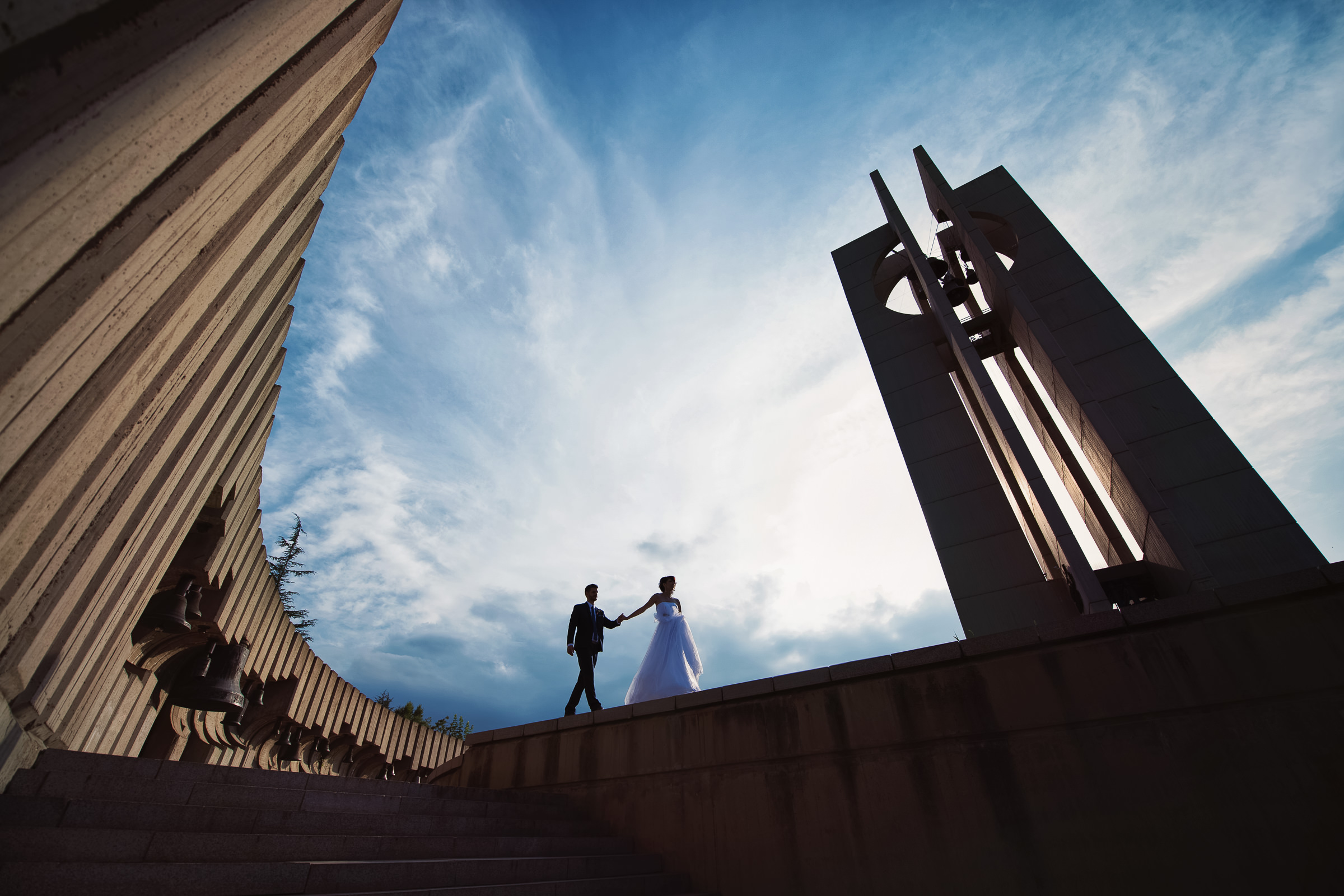 Couple with giant bell structure - photo by Deliysky Studio