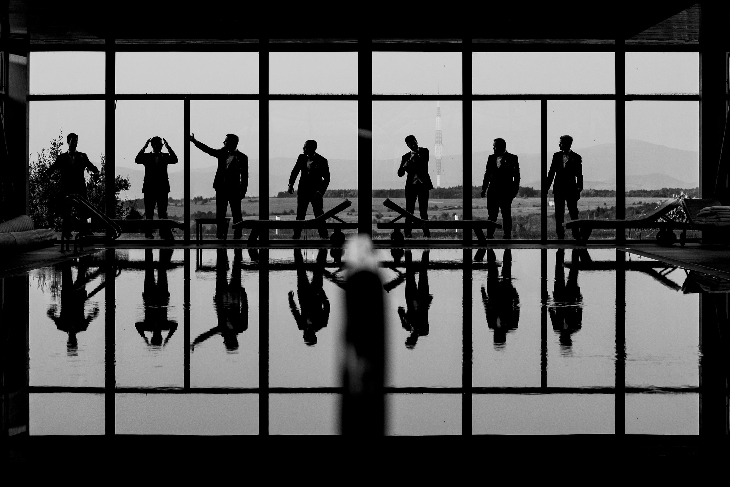 Silhouettes of grooms reflected in pool - photo by Deliysky Studio
