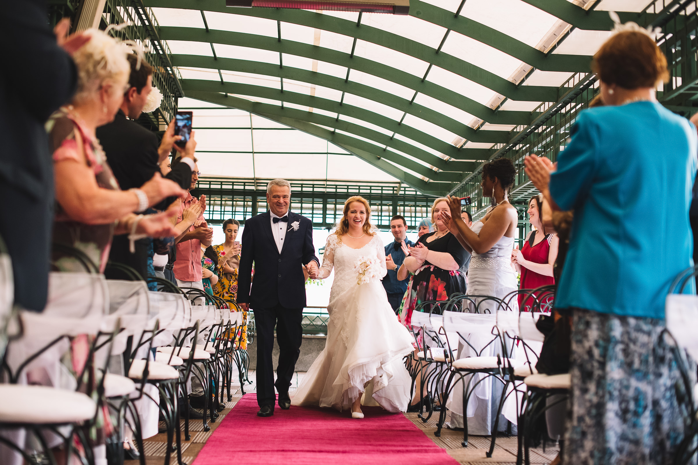 Guests applaud couple walking down aisle - photo by Deliysky Studio