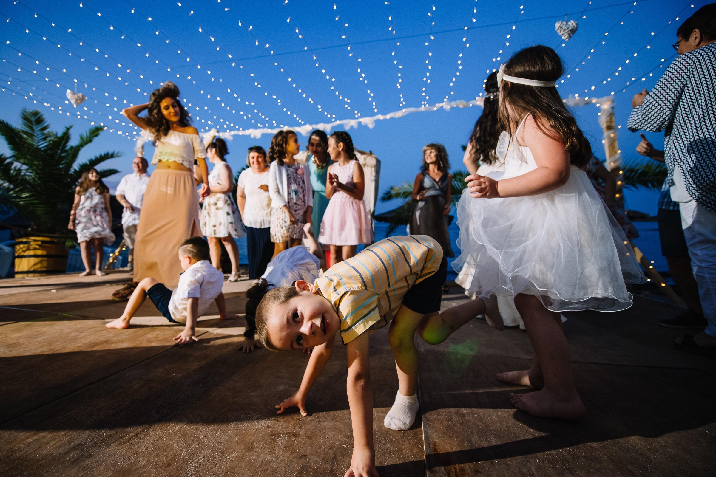 Kid fun under strings of light - photo by Deliysky Studio