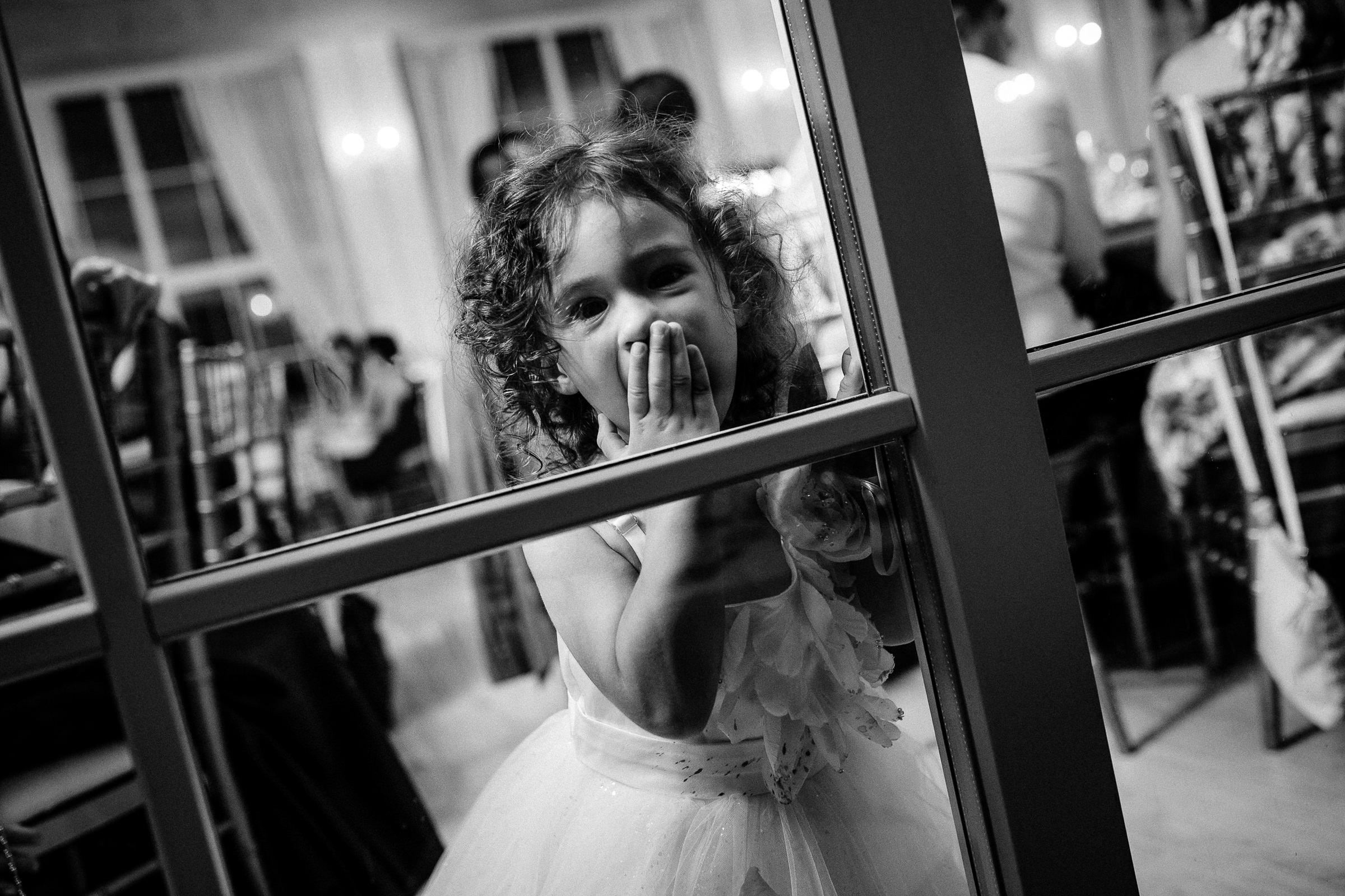 Little girl looking through glass door - photo by Deliysky Studio