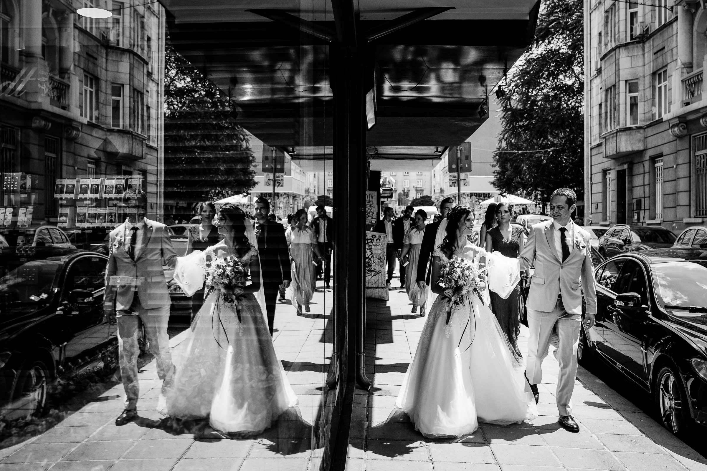 Reflected couple and guests in street scene - photo by Deliysky Studio