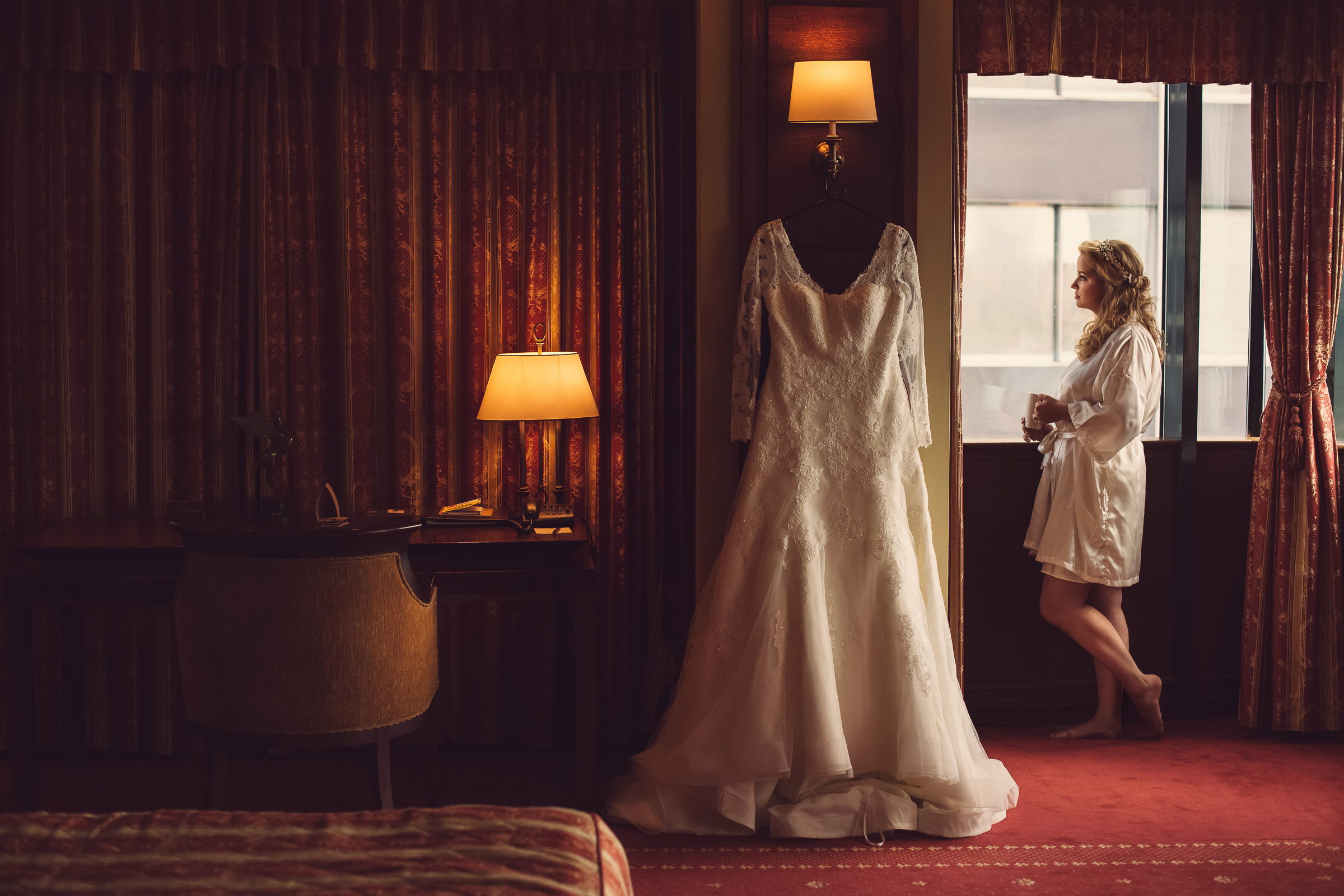 Robed bride with hanging gown - photo by Deliysky Studio