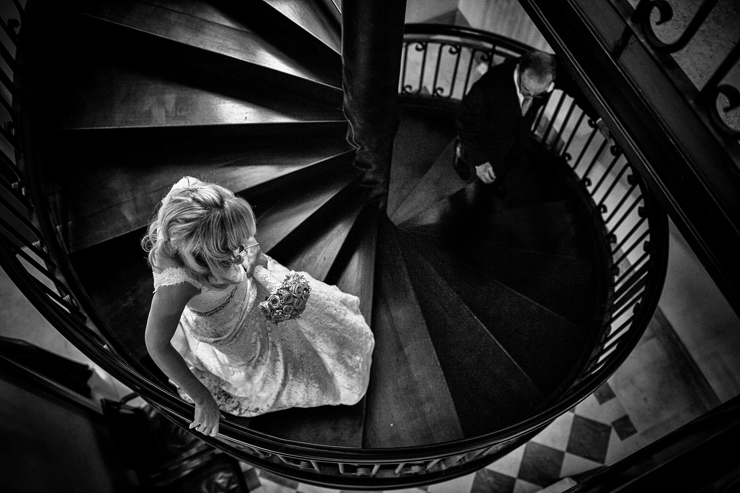 Bride and groom approach on spiral staircase - photo by Christophe Viseux Photography