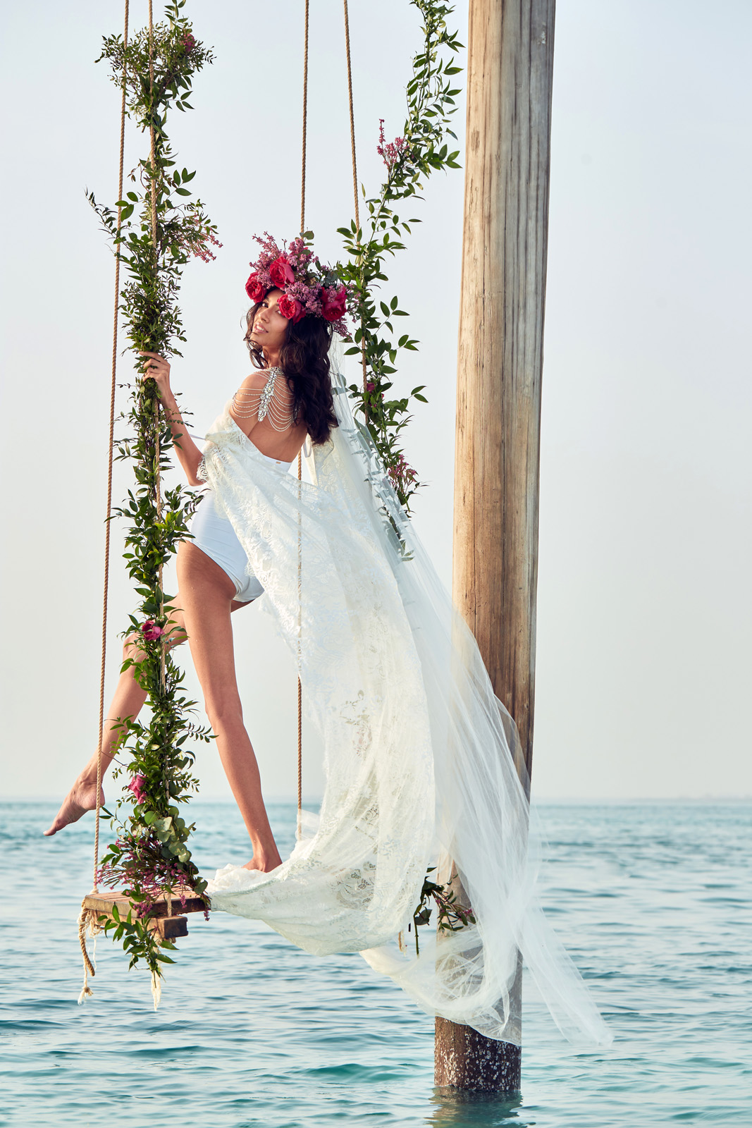 Swimsuit bride on decorated swing - photo by Christophe Viseux Photography