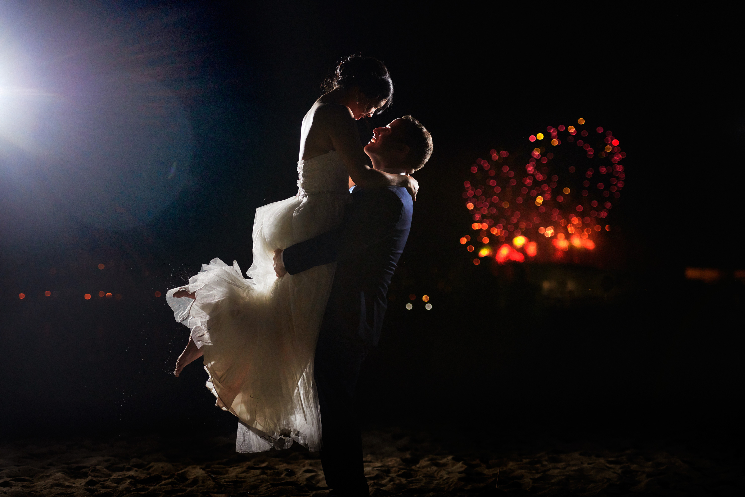 Groom lifts bride against fireworks - photo by Jozef Povazan Photography