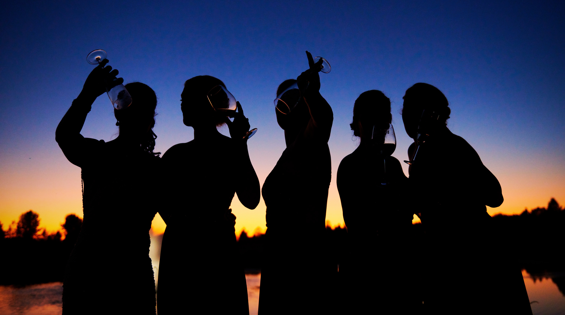Silhouette of bridesmaids drinking wine at sunset - photo by Jozef Povazan Photography