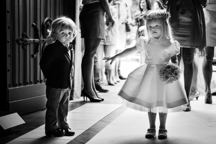 Adorable flower girl helps brother down the aisle - photo by Yves Schepers