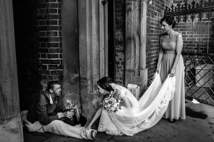 Black and white photo of compassionate bride and homeless man by Yves Schepers