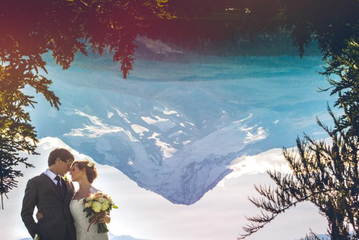 Couple portrait with reflected snow-capped mountain by Jeff Newsom
